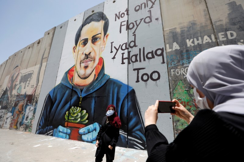 A Palestinian woman takes pictures of her friend posing in front of the Israeli barrier with a mural depicting Iyad al-Halaq, an unarmed and autistic Palestinian who was shot dead by Israeli police, in Bethlehem in the Israeli-occupied West Bank June 18, 2020. REUTERS/Mussa Qawasma/File Photo