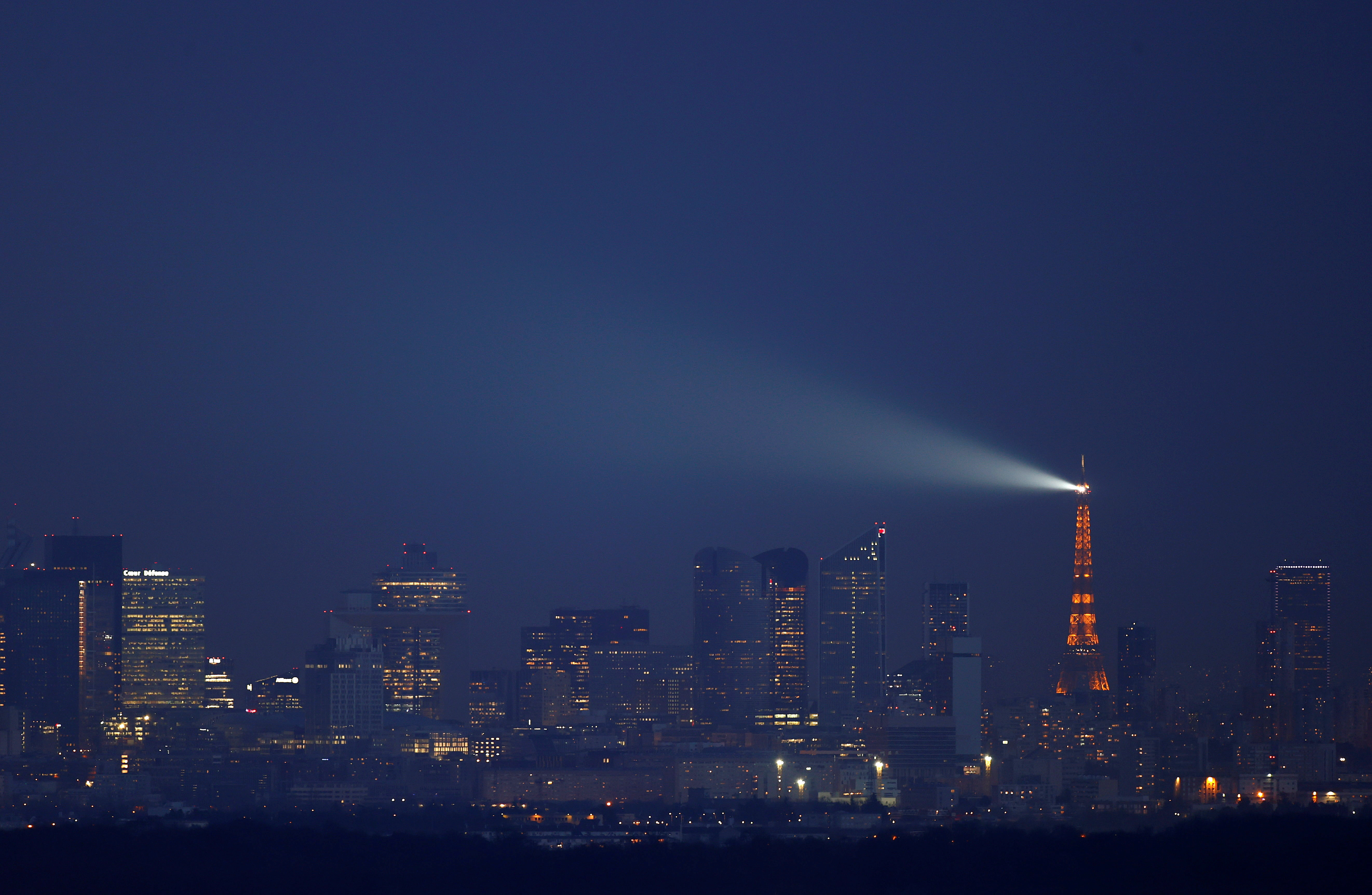 The Eiffel Tower lights the sky behind the financial district of La Defense during a nationwide curfew, from 6 p.m to 6 a.m, due to tighter measures against the spread of the coronavirus disease (COVID-19) near Paris, France, February 24, 2021.   REUTERS/Christian Hartmann