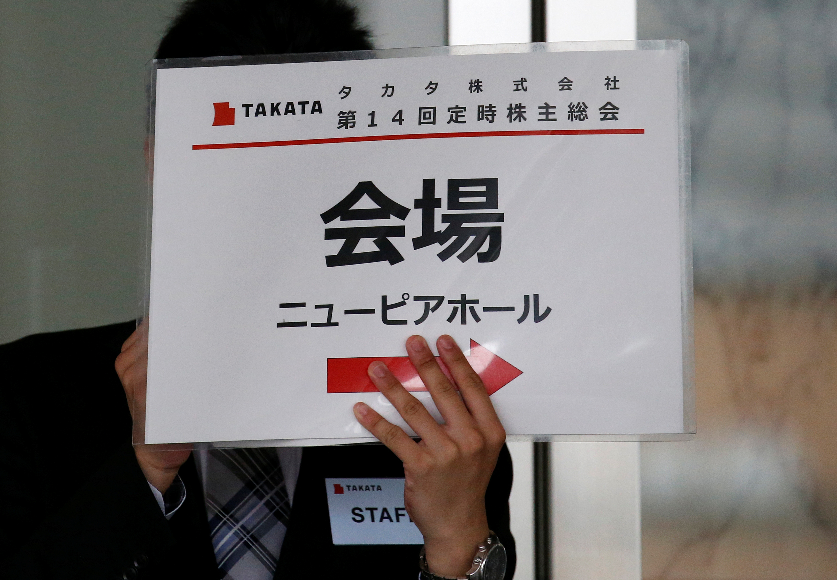 A staff member of Japanese auto parts maker Takata Corp. holds a signboard of the company's Annual General Meeting at an entrance of the venue in Tokyo, Japan,  June 27, 2017, following the company's  filing for bankruptcy protection. REUTERS/Issei Kato