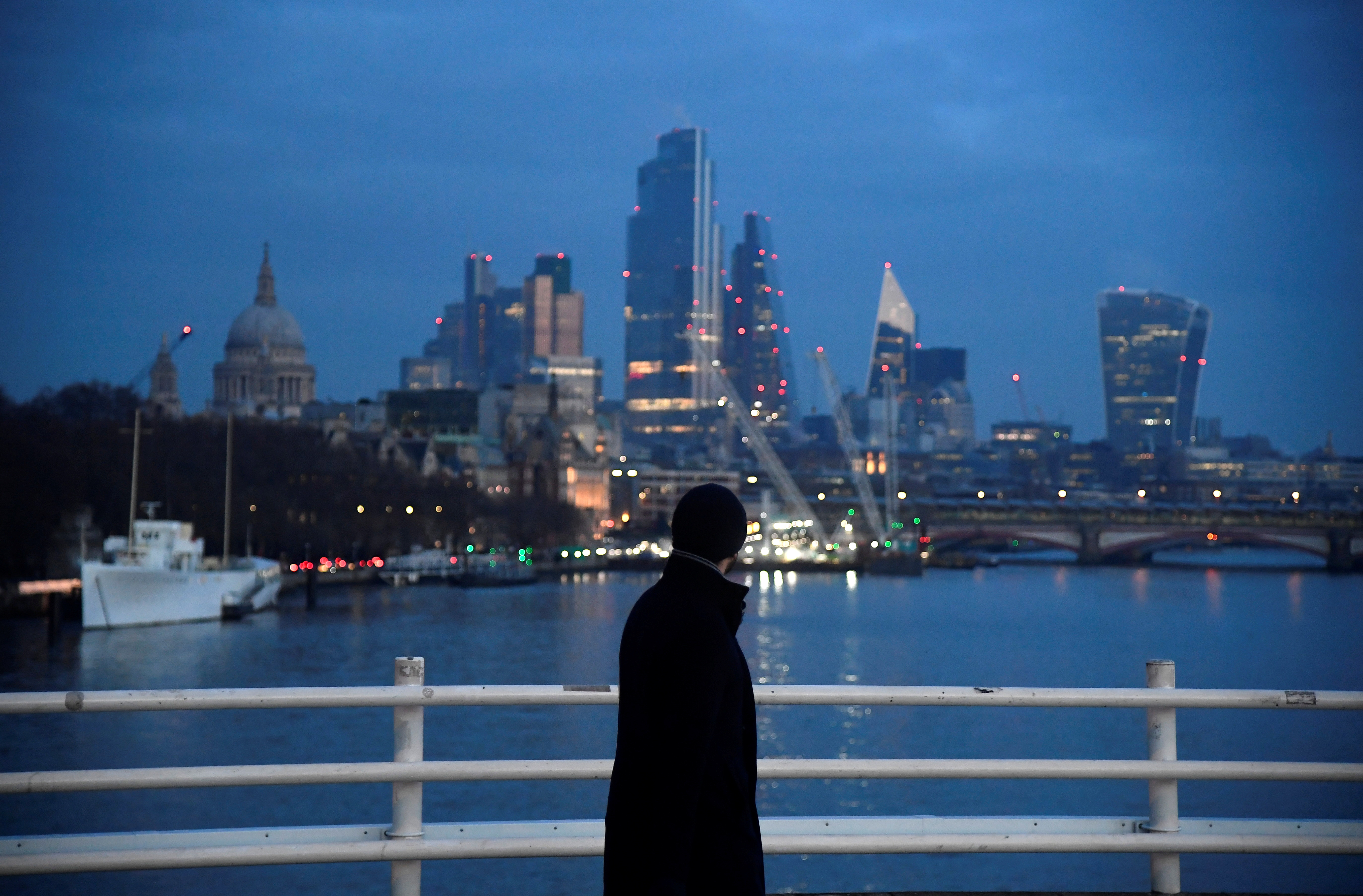 A man looks towards skyscrapers of the City of London financial district as he crosses Waterloo Bridge, amid the coronavirus disease (COVID-19) pandemic, in London, Britain, January 15, 2021. REUTERS/Toby Melville