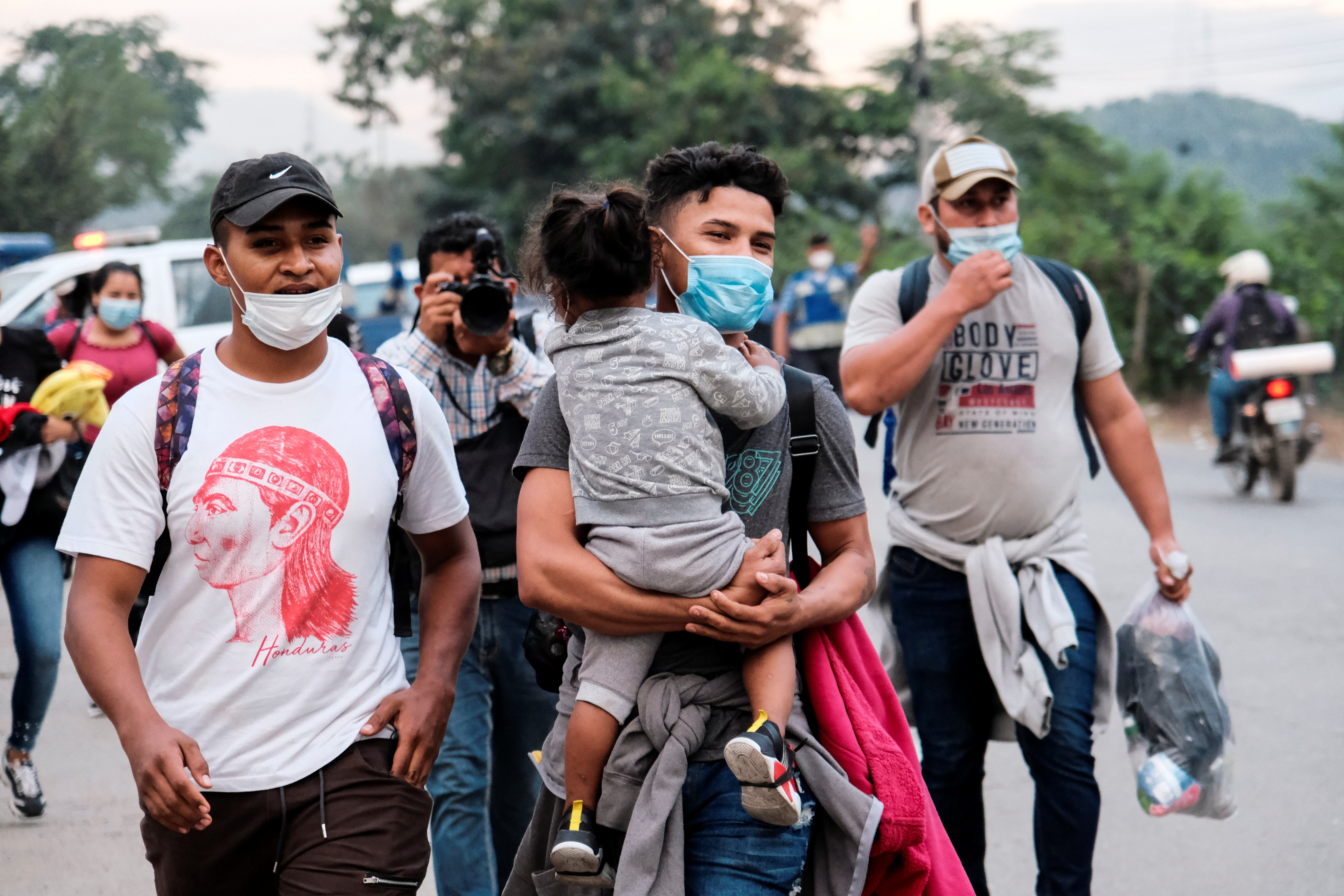A man carries his baby as he walks along other Hondurans in a new caravan of migrants, set to head to the United States, in San Pedro Sula, Honduras January 15, 2021. REUTERS/Yoseph Amaya