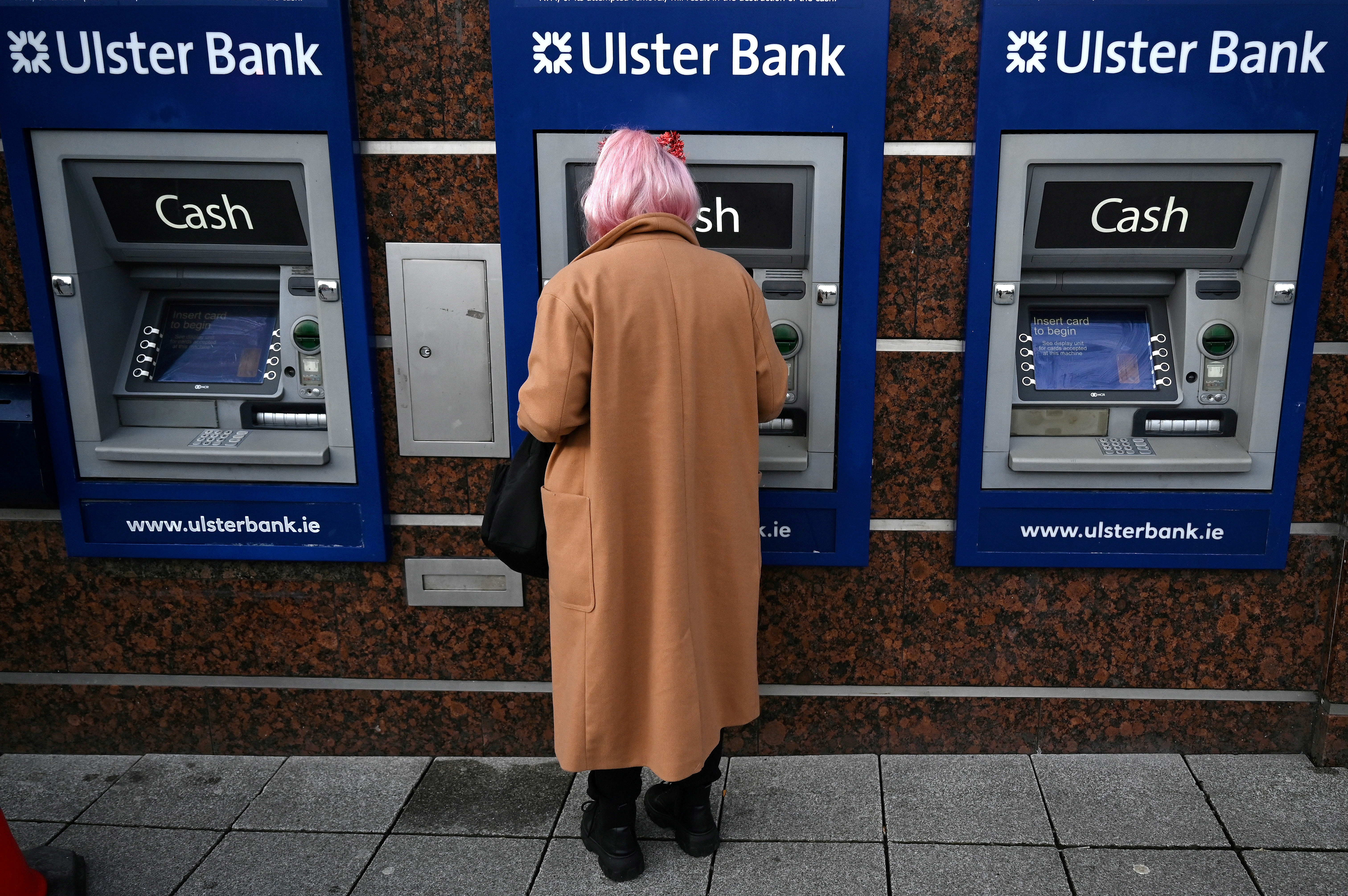 A woman uses an Ulster Bank ATM to take out cash amid the spread of the coronavirus disease (COVID-19) pandemic, in Galway, Ireland, December 22, 2020. REUTERS/Clodagh Kilcoyne/File Photo
