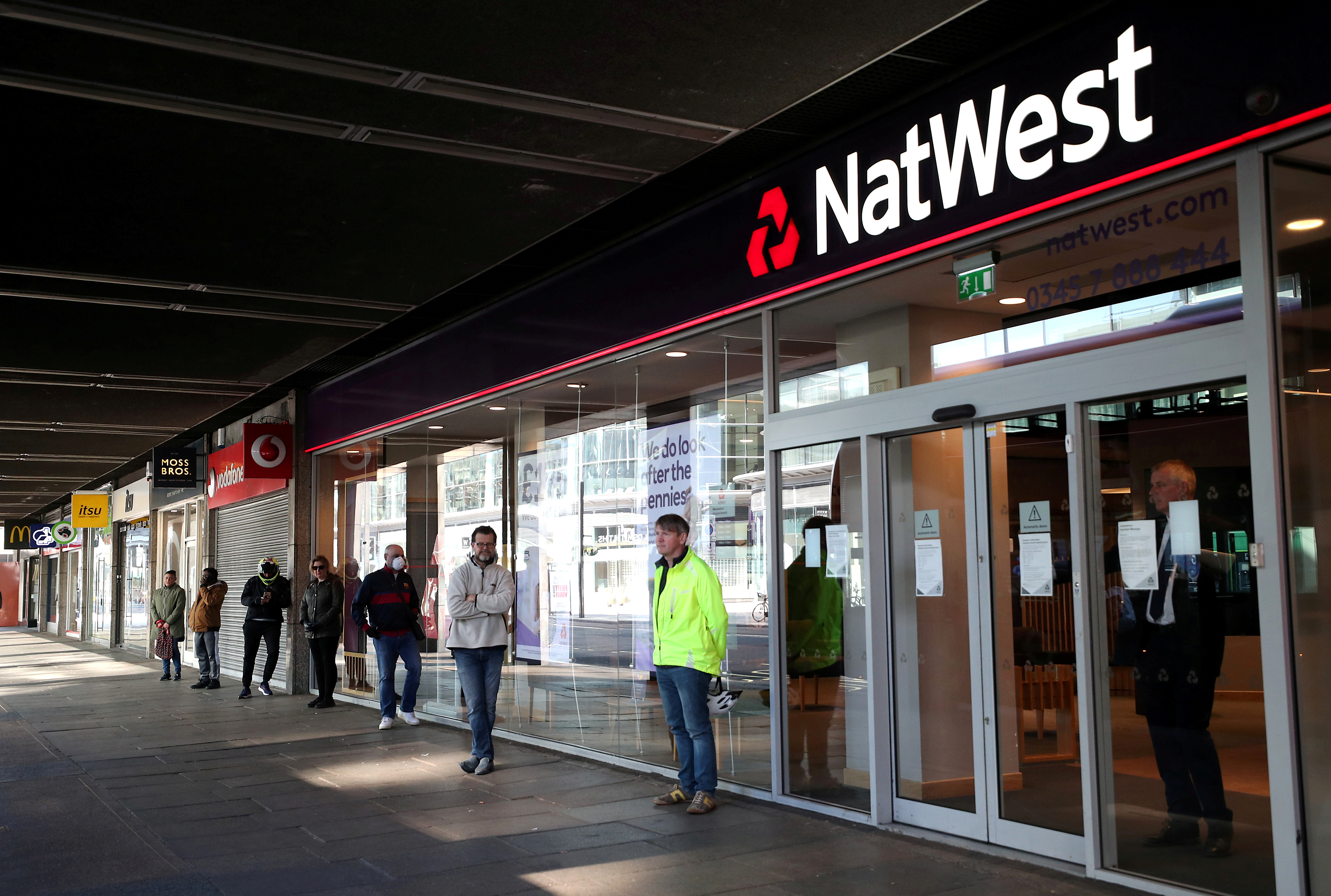 People maintain social distance while they queue outside a Natwest bank as the spread of the coronavirus disease (COVID-19) continues, in London, Britain, March 26, 2020. REUTERS/Hannah McKay/File Photo