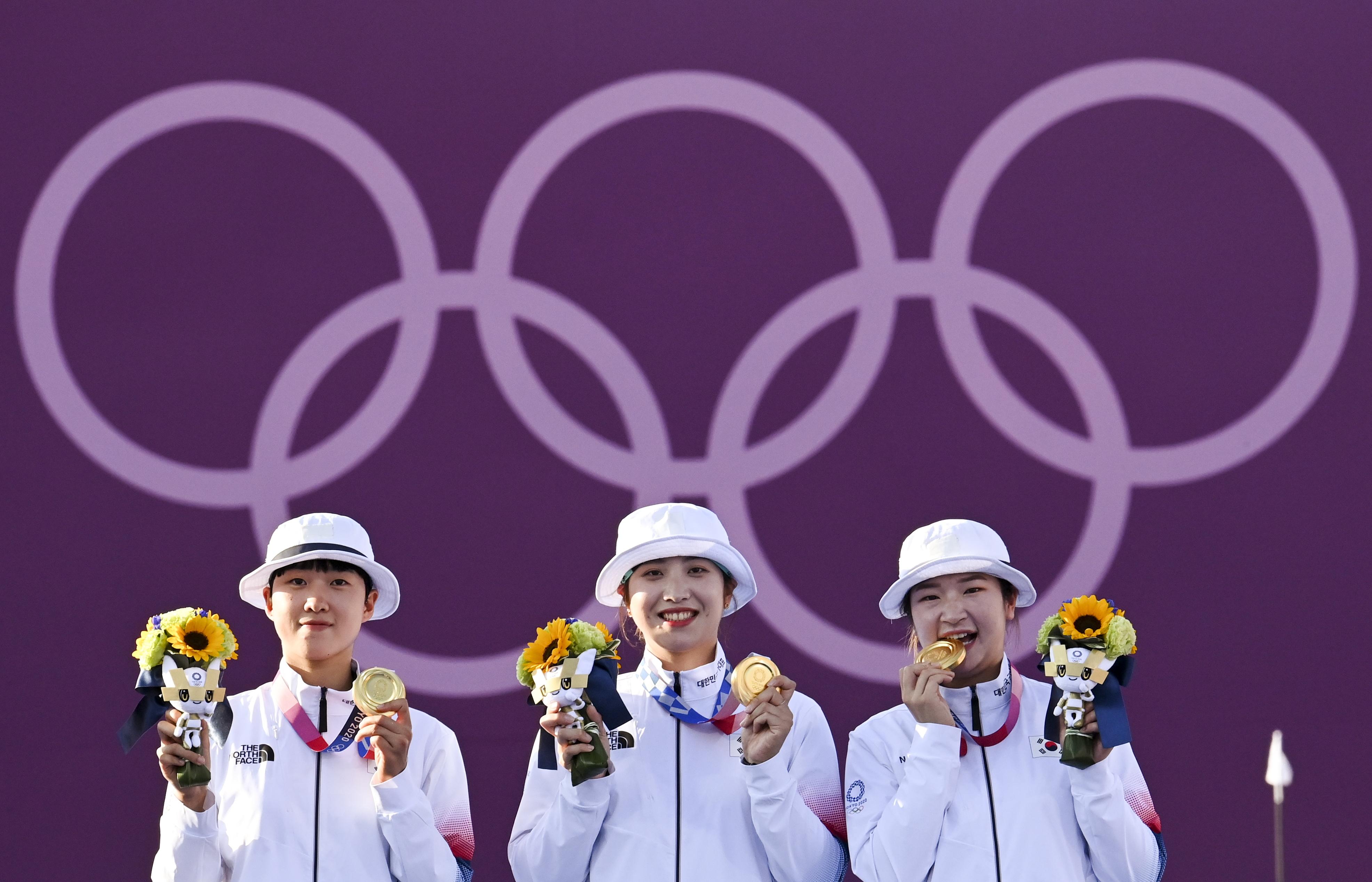 Tokyo 2020 Olympics - Archery - Women's Team - Medal Ceremony – Yumenoshima Archery Field, Tokyo, Japan July 25, 2021. Gold medallist An San of South Korea, gold medallist Jang Minhee of South Korea and gold medallist Kang Chae Young of South Korea celebrate on the podium. REUTERS/Clodagh Kilcoyne/File photo