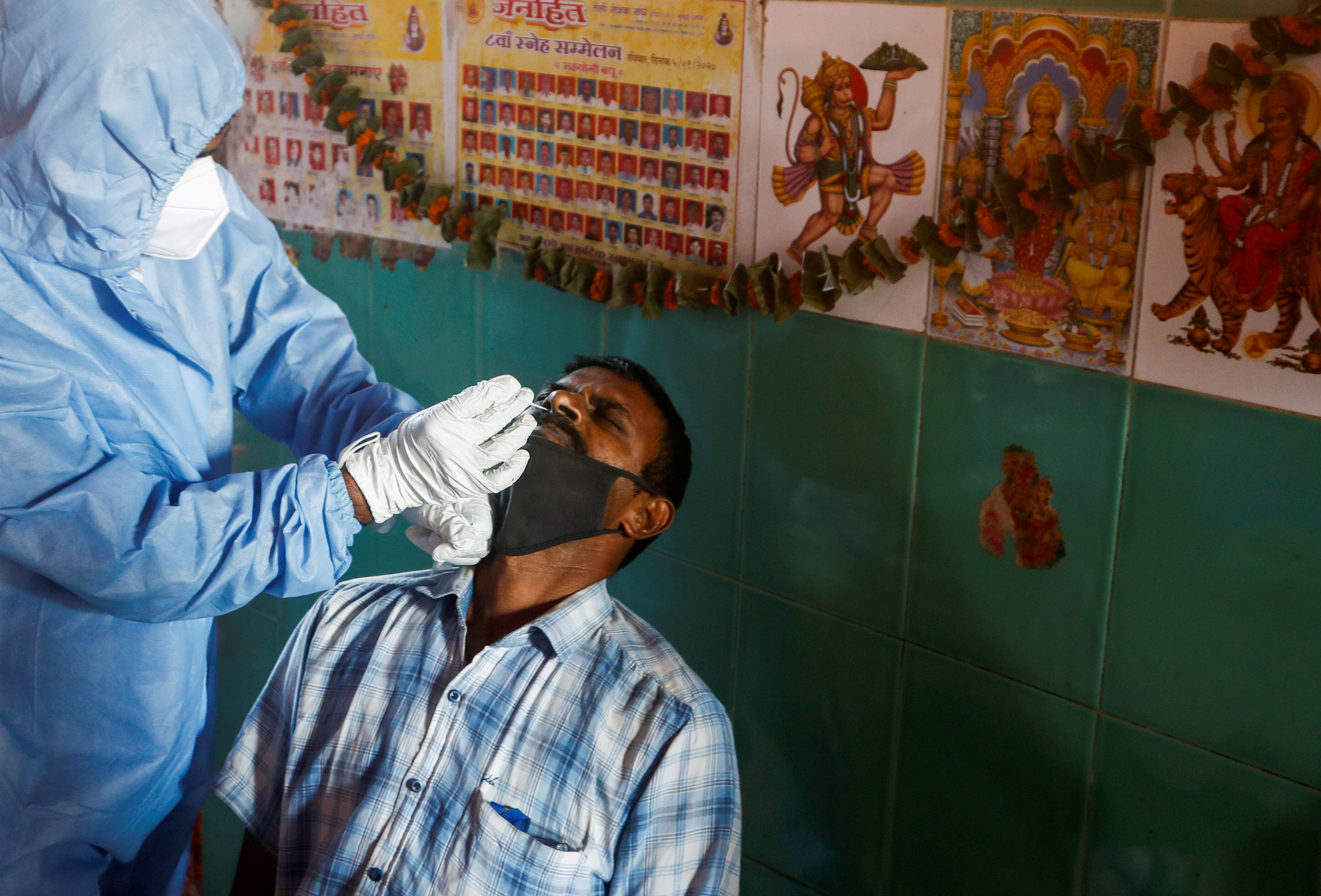 A health worker in personal protective equipment (PPE) collects a swab sample from a man during a rapid antigen testing campaign for the coronavirus disease (COVID-19), at a vegetable market in Mumbai, India, November 21, 2020. REUTERS/Francis Mascarenhas