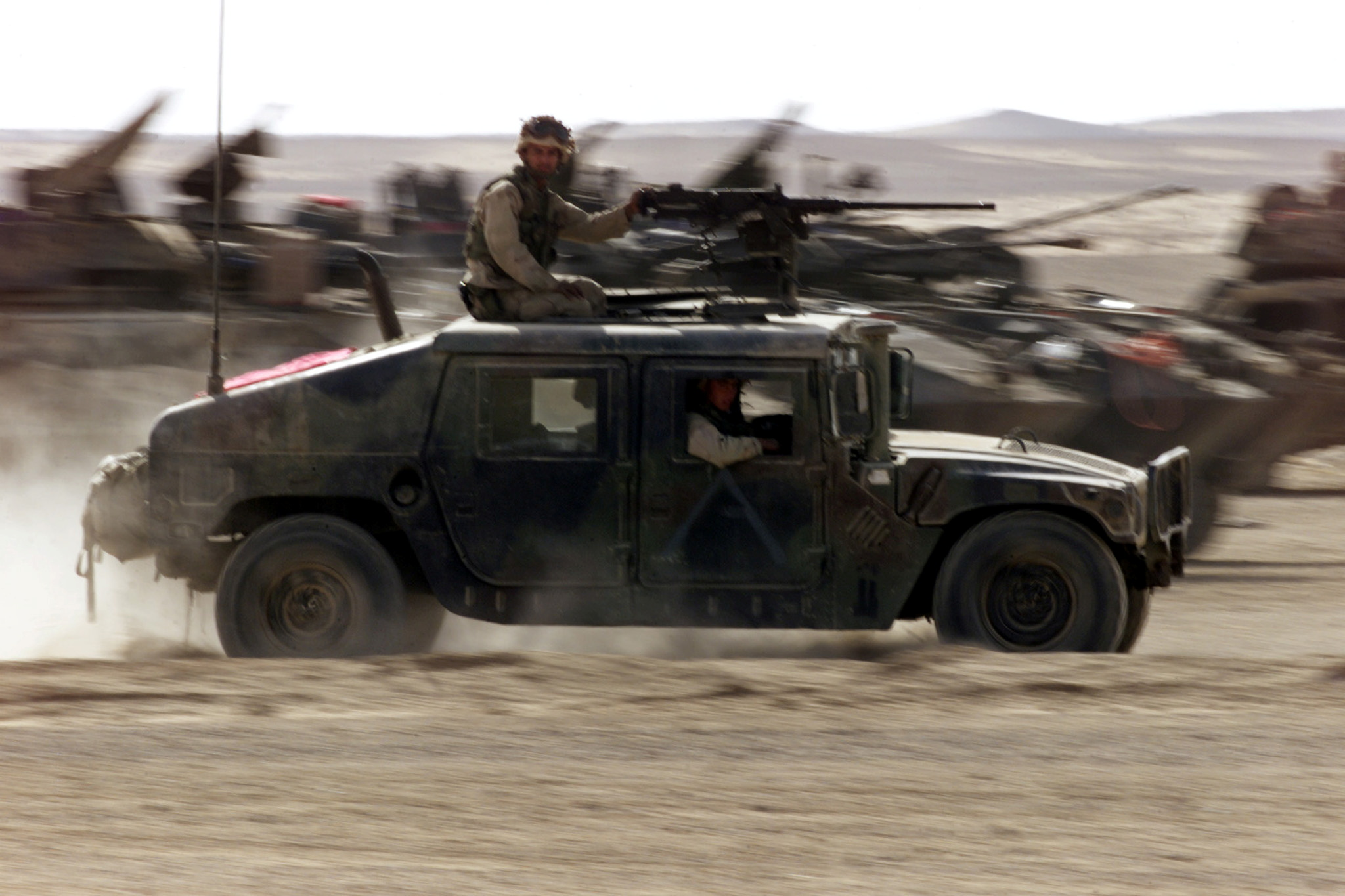 A U.S. Marine Humvee kicks up dust as it crosses a group of Marine LAVs (Light Armored Vehicles) as it leaves on patrol from a Marine base in southern Afghanistan December 2, 2001.   REUTERS/Jim Hollander/File Photo