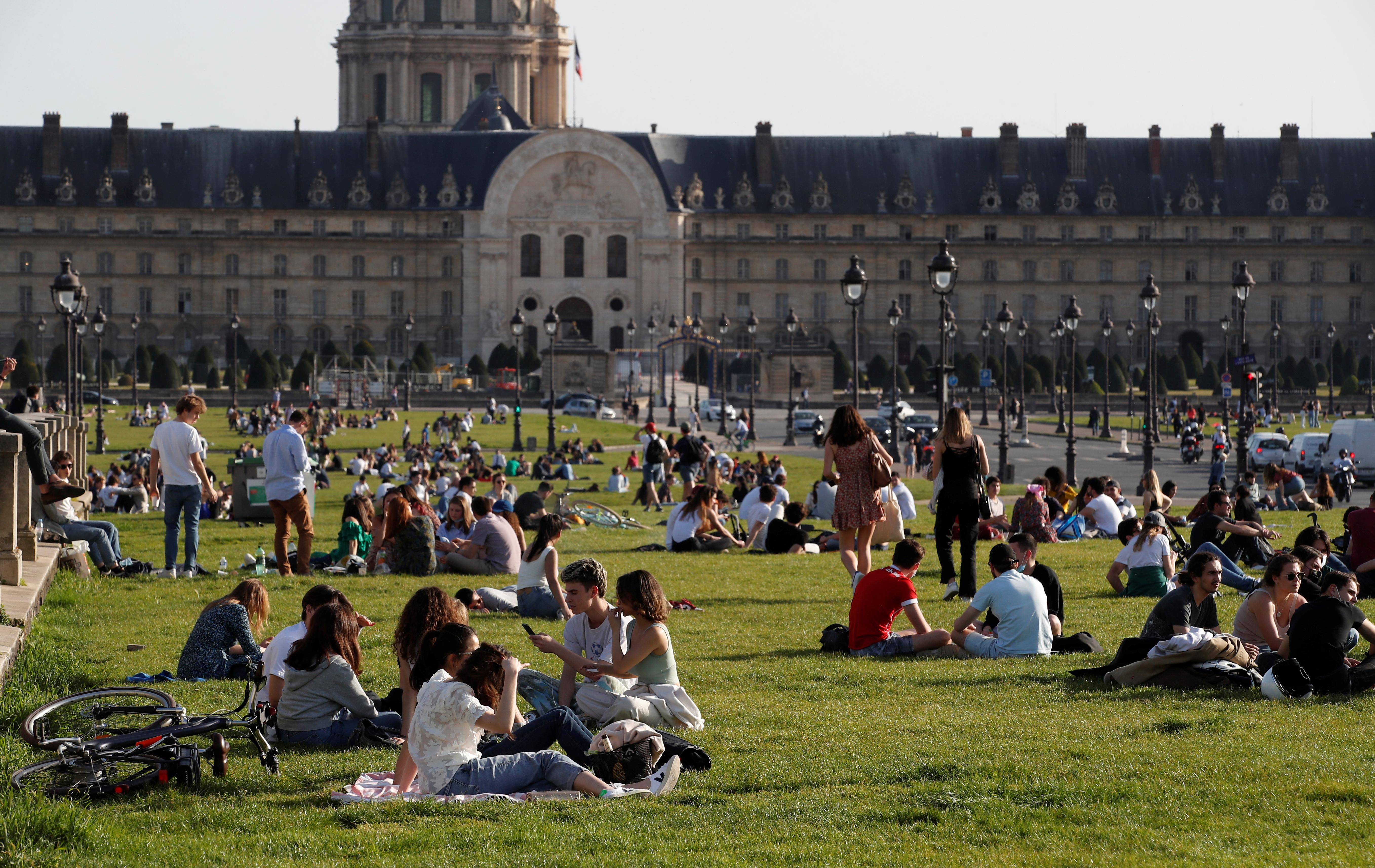 Mọi người tận hưởng thời tiết nắng ấm khi ngồi trên bãi cỏ gần điện Invalides ở Paris trong bối cảnh dịch bệnh do coronavirus (COVID-19) bùng phát ở Pháp, ngày 31 tháng 3 năm 2021. REUTERS / Gonzalo Fuentes