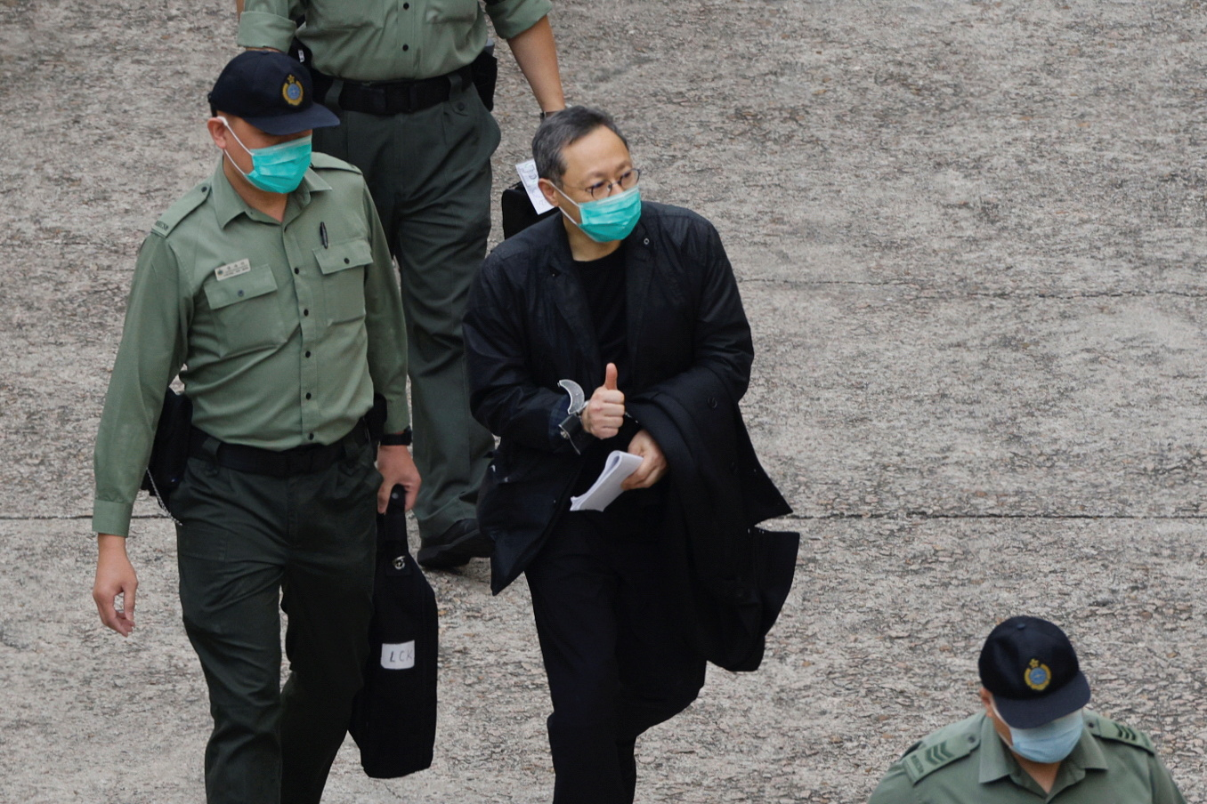 Pro-democracy activist Benny Tai flashes thumbs up as he walks to a prison van to head to court, over the national security law charge, in the early morning, in Hong Kong, China March 2, 2021. REUTERS/Tyrone Siu