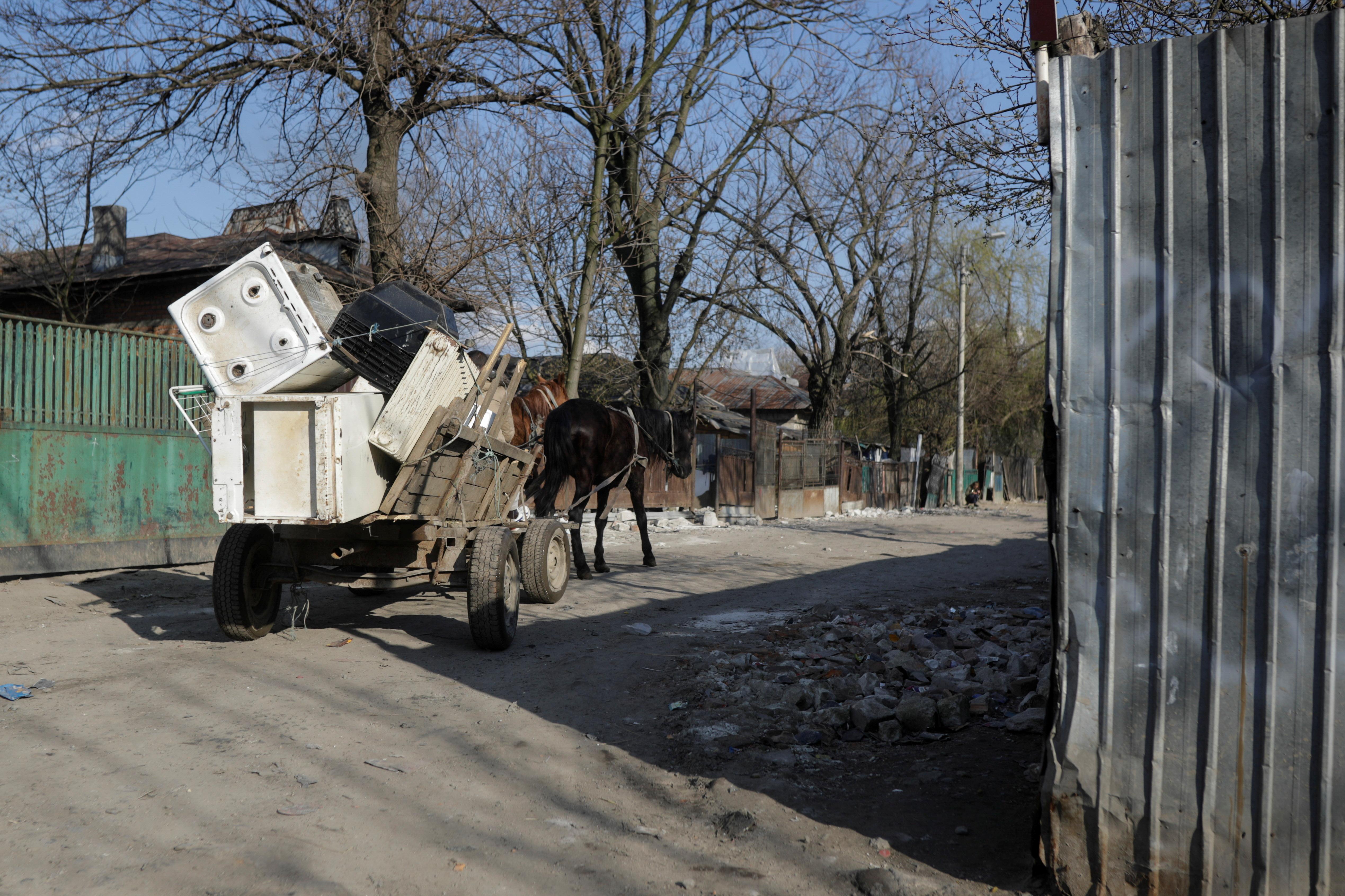 A horse-drawn carriage carries domestic appliance waste on the mud street of Sintesti village, Ilfov, Romania, April 9, 2021.Inquam Photos/George Calin via REUTERS