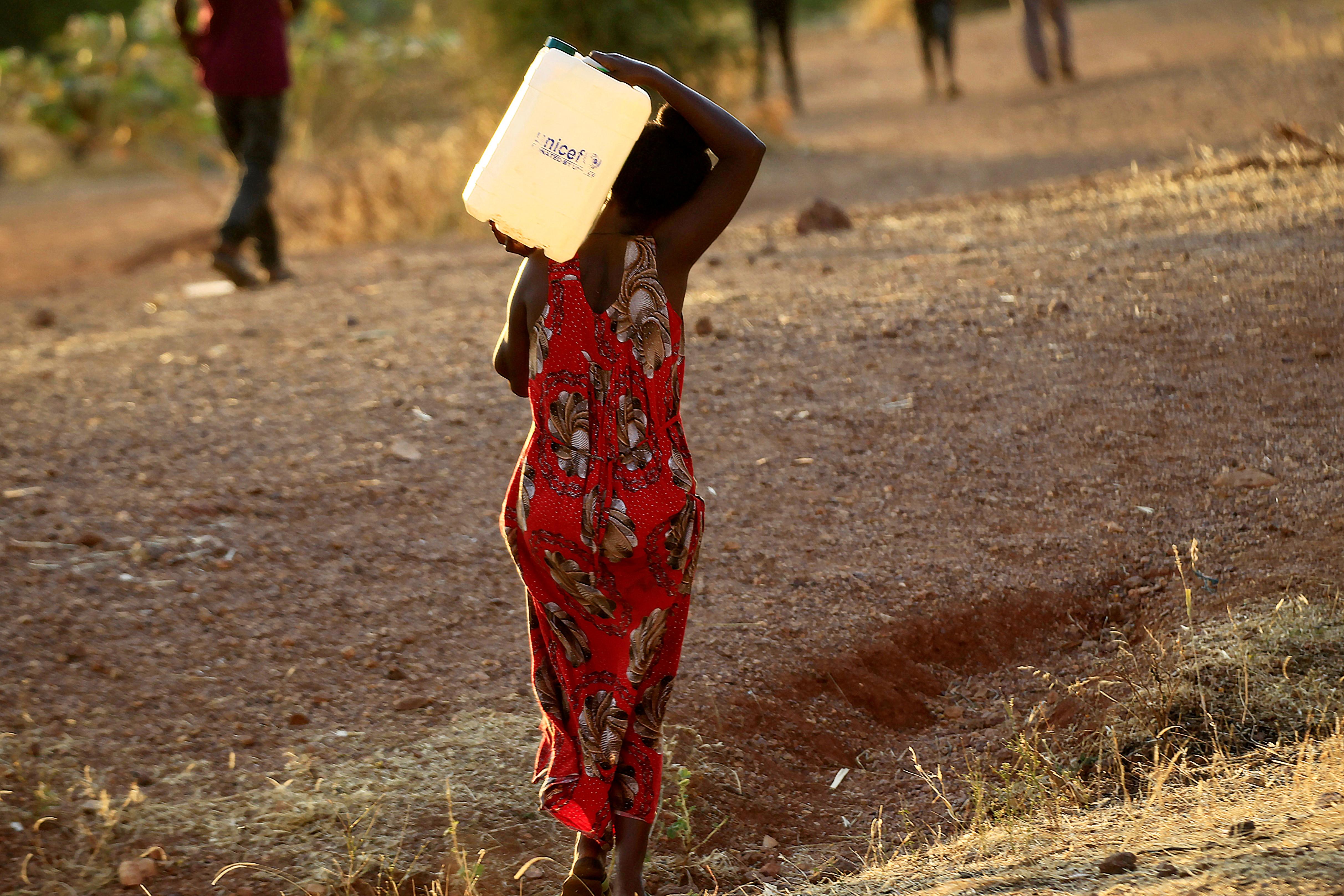 An Ethiopian woman who fled war in Tigray region carries a jerrycan of water as she walks at the Um-Rakoba camp on the Sudan-Ethiopia border in Al-Qadarif state, Sudan November 19, 2020. REUTERS/Mohamed Nureldin Abdallah/File Photo