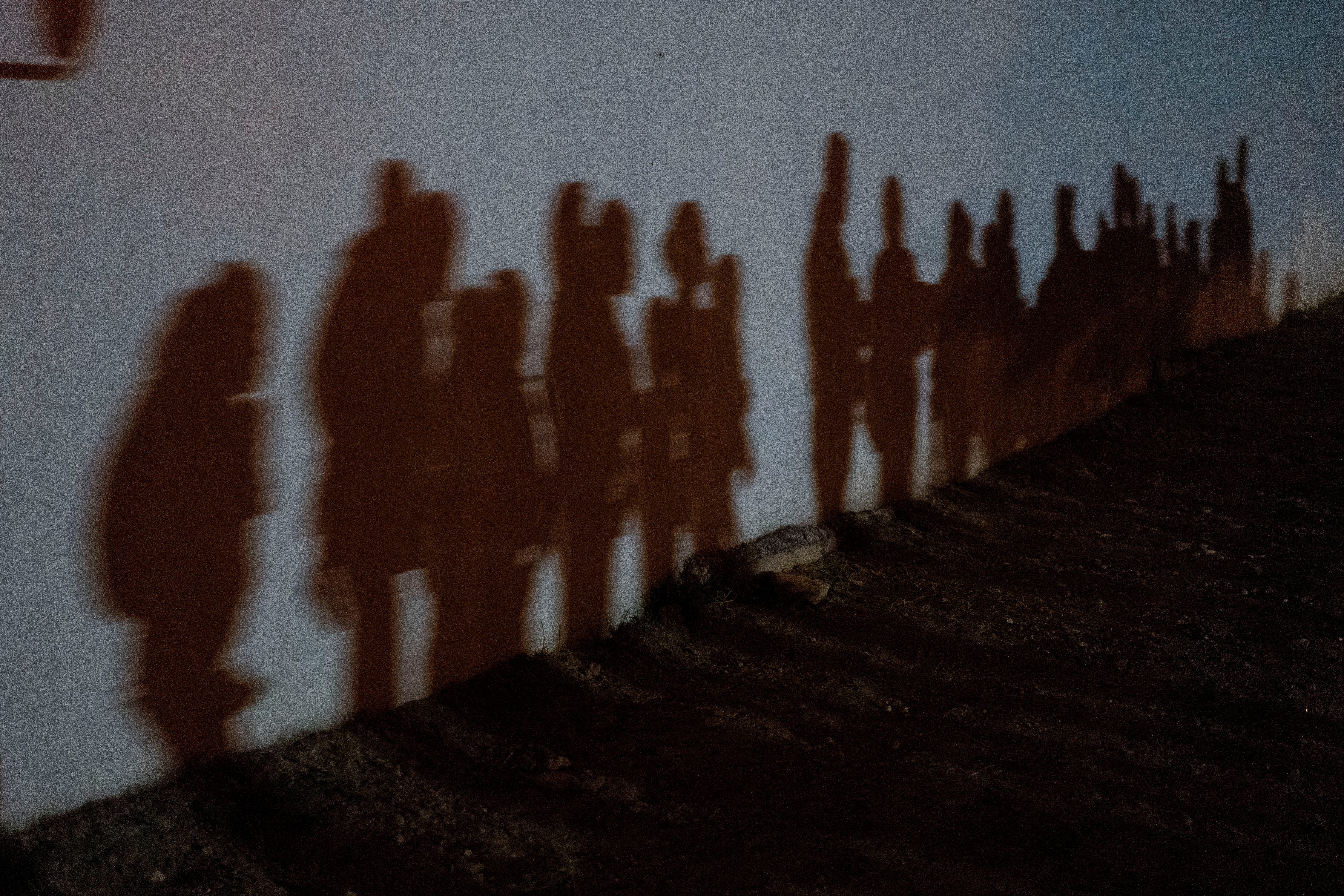 Asylum-seeking migrant families cast shadows on a wall as they form a queue to be processed by the U.S. Border Patrol after crossing the Rio Grande river into the United States from Mexico in Roma, Texas, U.S., August 12, 2021. REUTERS/Go Nakamura