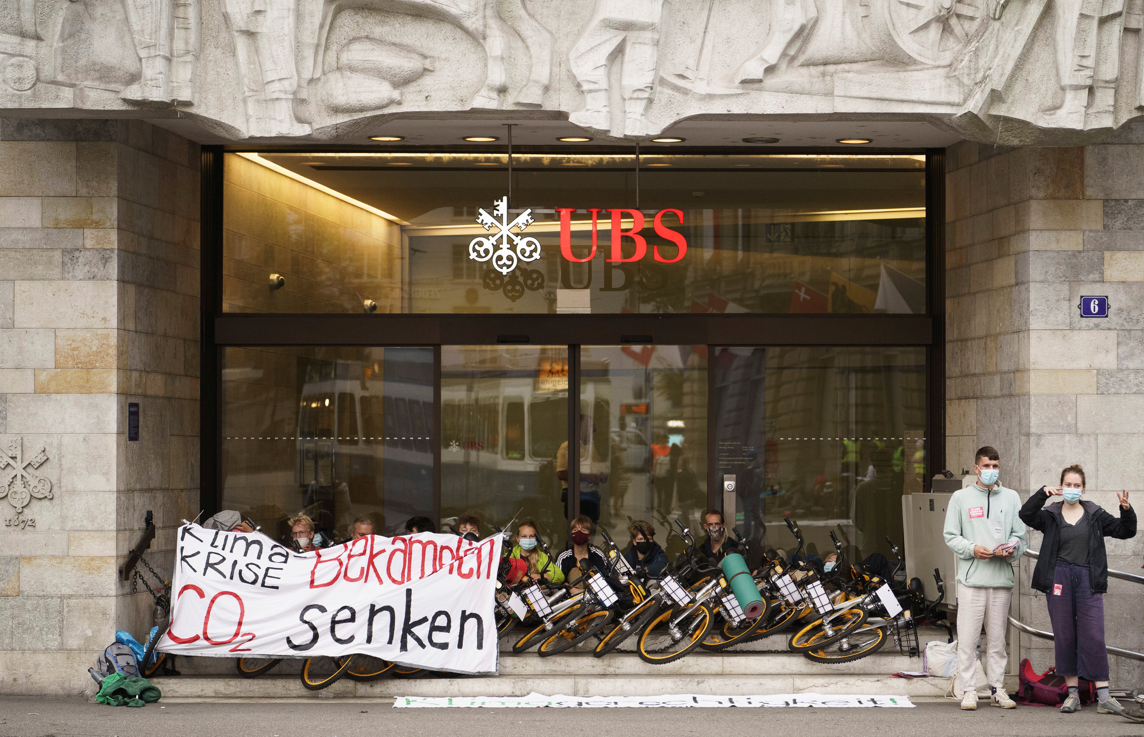 """Climate activists of """"Rise up for Change"""" block an entrance of UBS to protest against big banks' financing of fossil fuel projects that damage the environment in Zurich, Germany, August 2, 2021. Schweiz Rise Up For Change/Handout via REUTERS"""