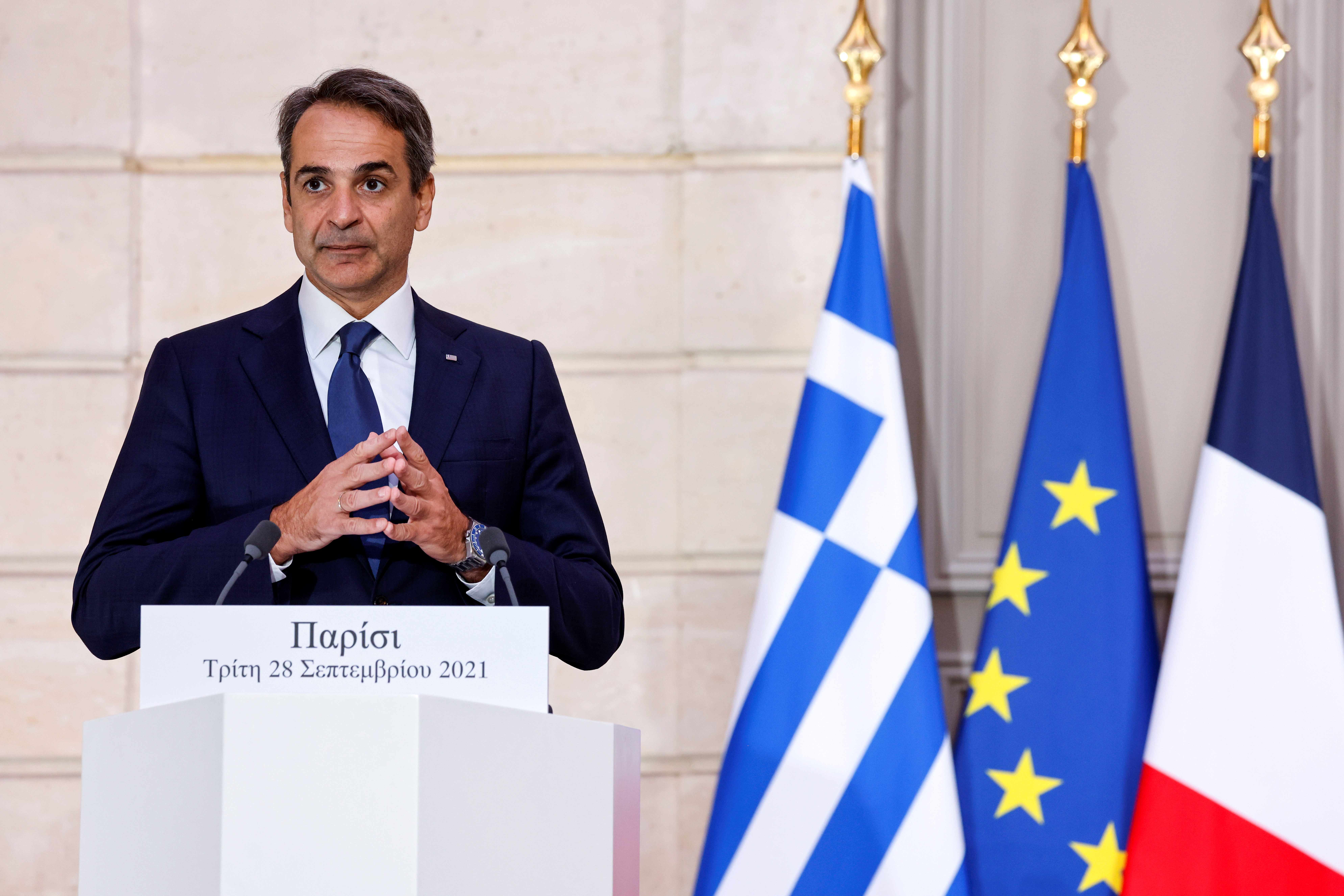 Greek Prime Minister Kyriakos Mitsotakis speaks as the French President listens on, during a signing ceremony of a new defence deal at The Elysee Palace in Paris, France September 28, 2021. Ludovic Marin/Pool via REUTERS