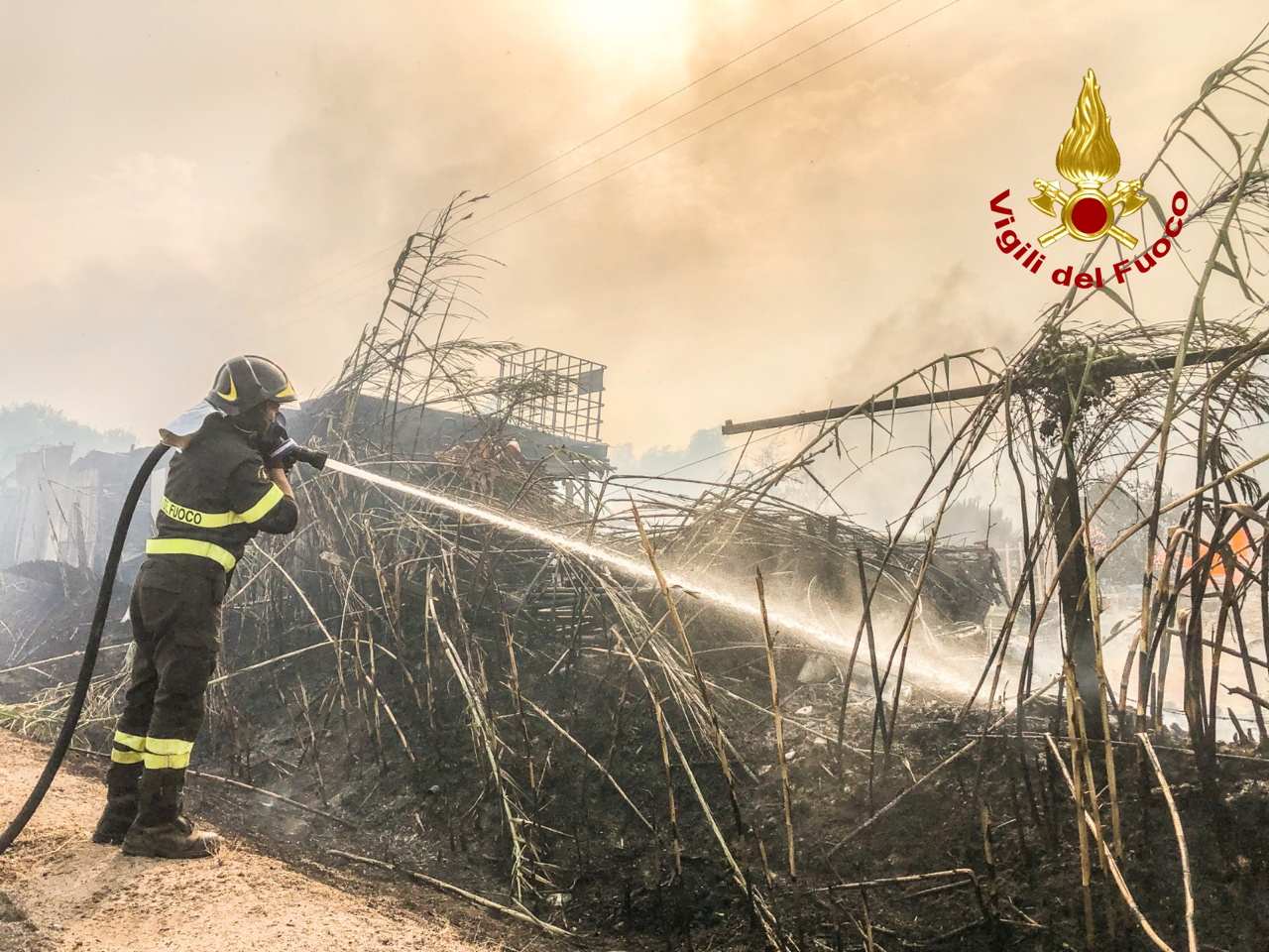 A firefighter battles the flames after a large wildfire broke out near Santu Lussurgiu, Sardinia, Italy July 24, 2021. Vigili del Fuoco/Handout via REUTERS