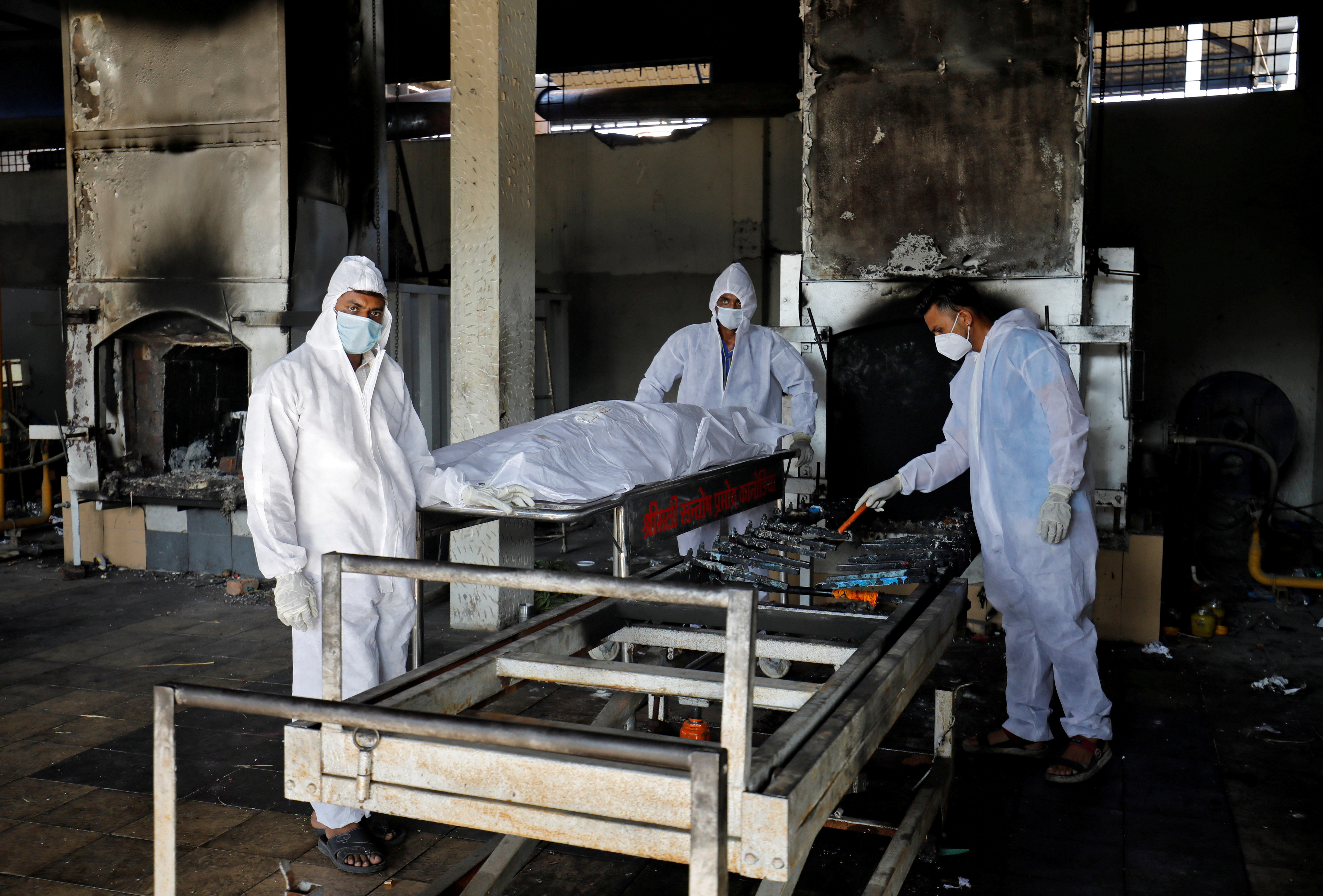 Volunteers from the Khan Trust prepare to cremate the body of a person who died from the coronavirus disease (COVID-19), at the Kurukshetra Crematorium in Surat, India, May 11, 2021.  REUTERS/Amit Dave/File Photo