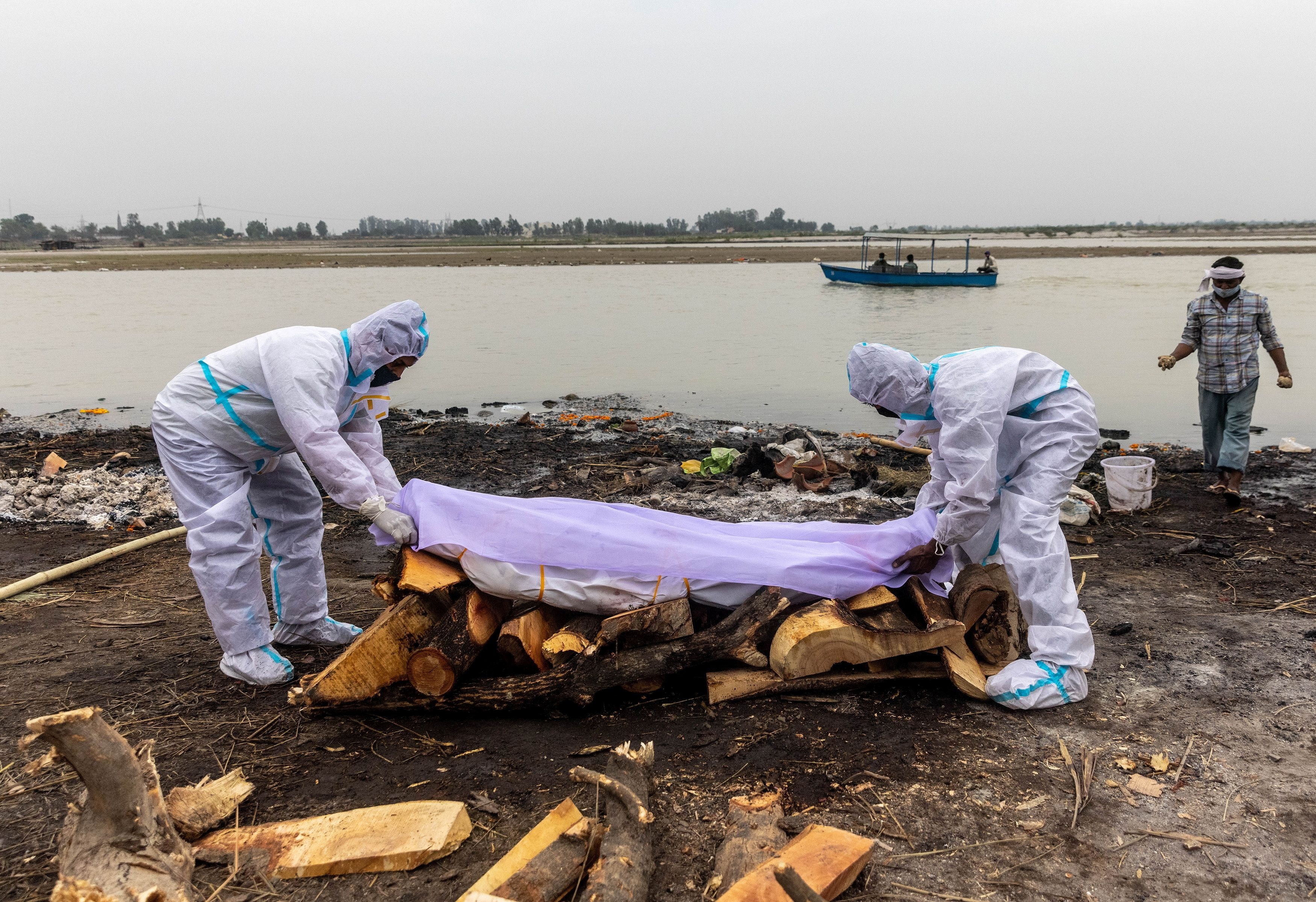 Men wearing protective suits place a white cloth over the body their relative, who died from the coronavirus disease (COVID-19), before his cremation on the banks of the river Ganges at Garhmukteshwar in the northern state of Uttar Pradesh, India, May 6, 2021. REUTERS/Danish Siddiqui