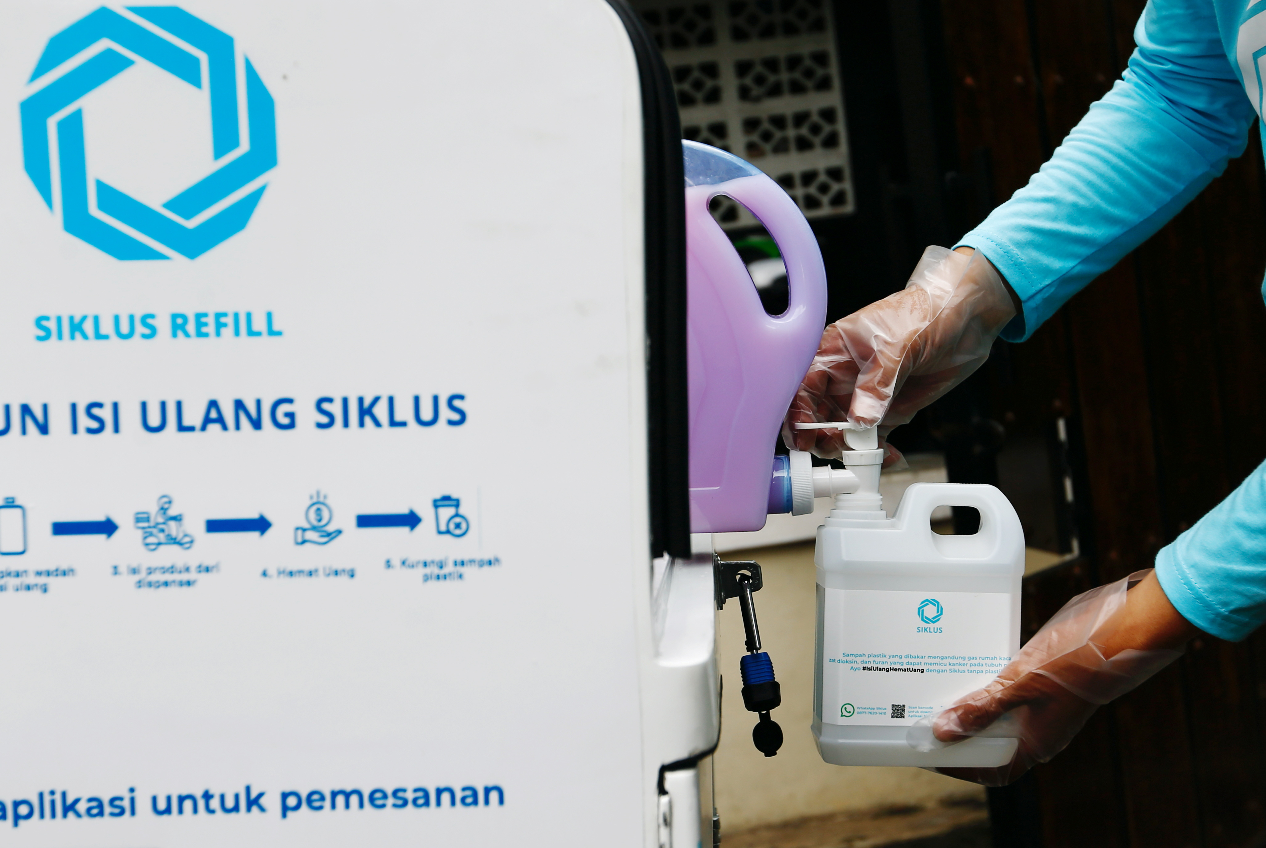 A worker at Siklus, a start-up company which refills household products in a bid to reduce plastic waste, refills a jerry can with cleaning liquid for a customer in Jakarta, Indonesia, May 19, 2021. Picture taken May 19, 2021 REUTERS/Ajeng Dinar Ulfiana