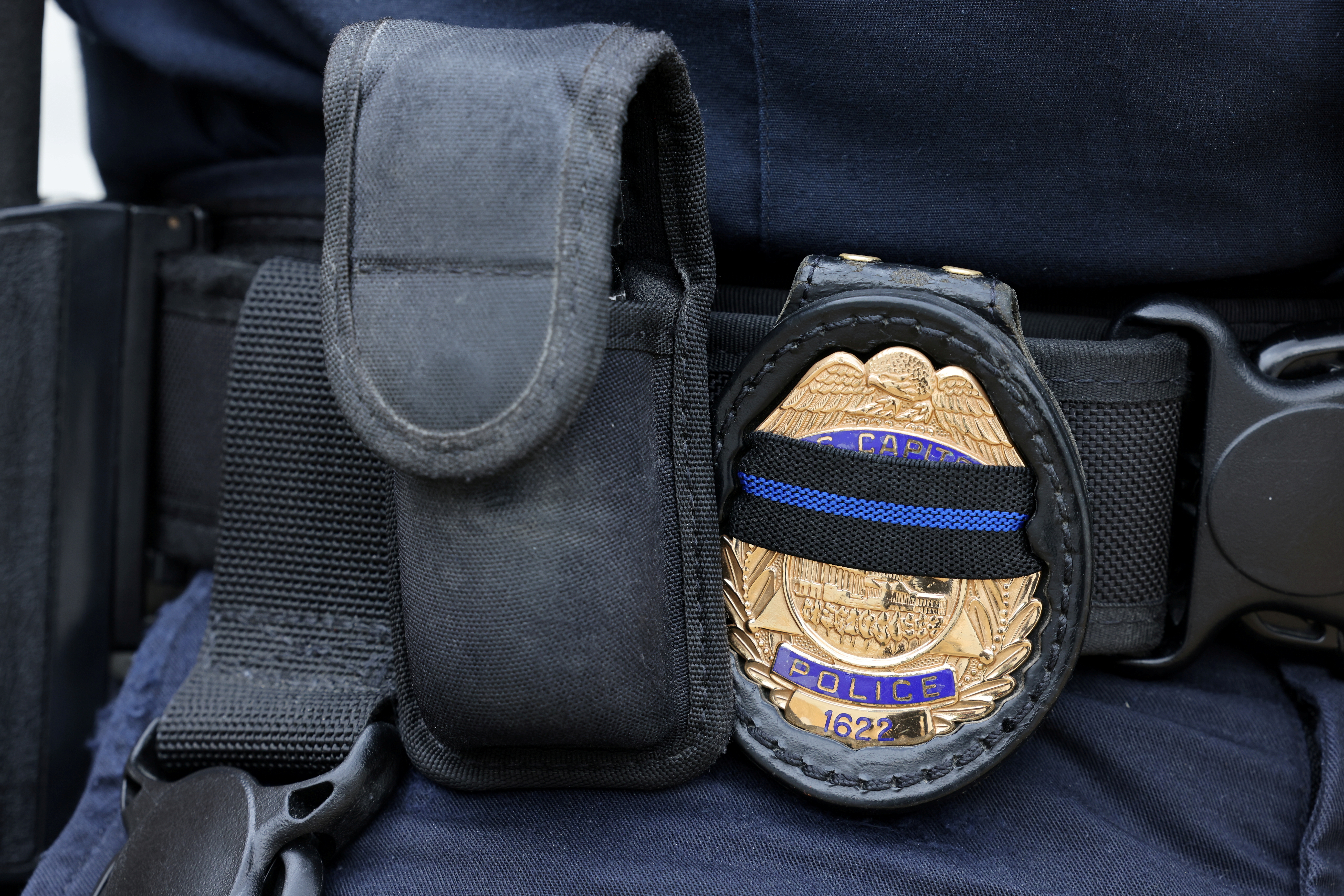 A U.S. Capitol police officer's badge shows a black stripe in honor of deceased colleagues as he guards the building on Capitol Hill in Washington, May 28, 2021.  REUTERS/Evelyn Hockstein/File Photo