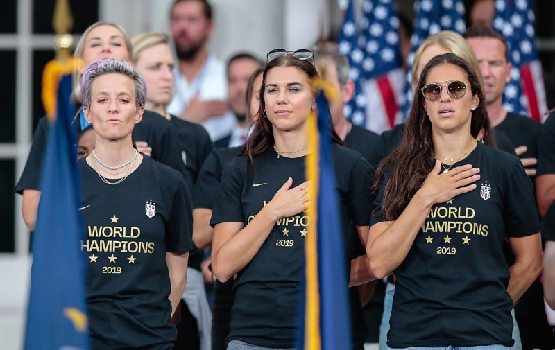 Jul 10, 2019; New York, NY, USA; United States women's soccer player Megan Rapinoe, left, and Alex Morgan, center, and Carli Lloyd stand during the national anthem at the ceremony at City Hall after winning the 2019 FIFA World Cup. Mandatory Credit: Vincent Carchietta-USA TODAY Sports