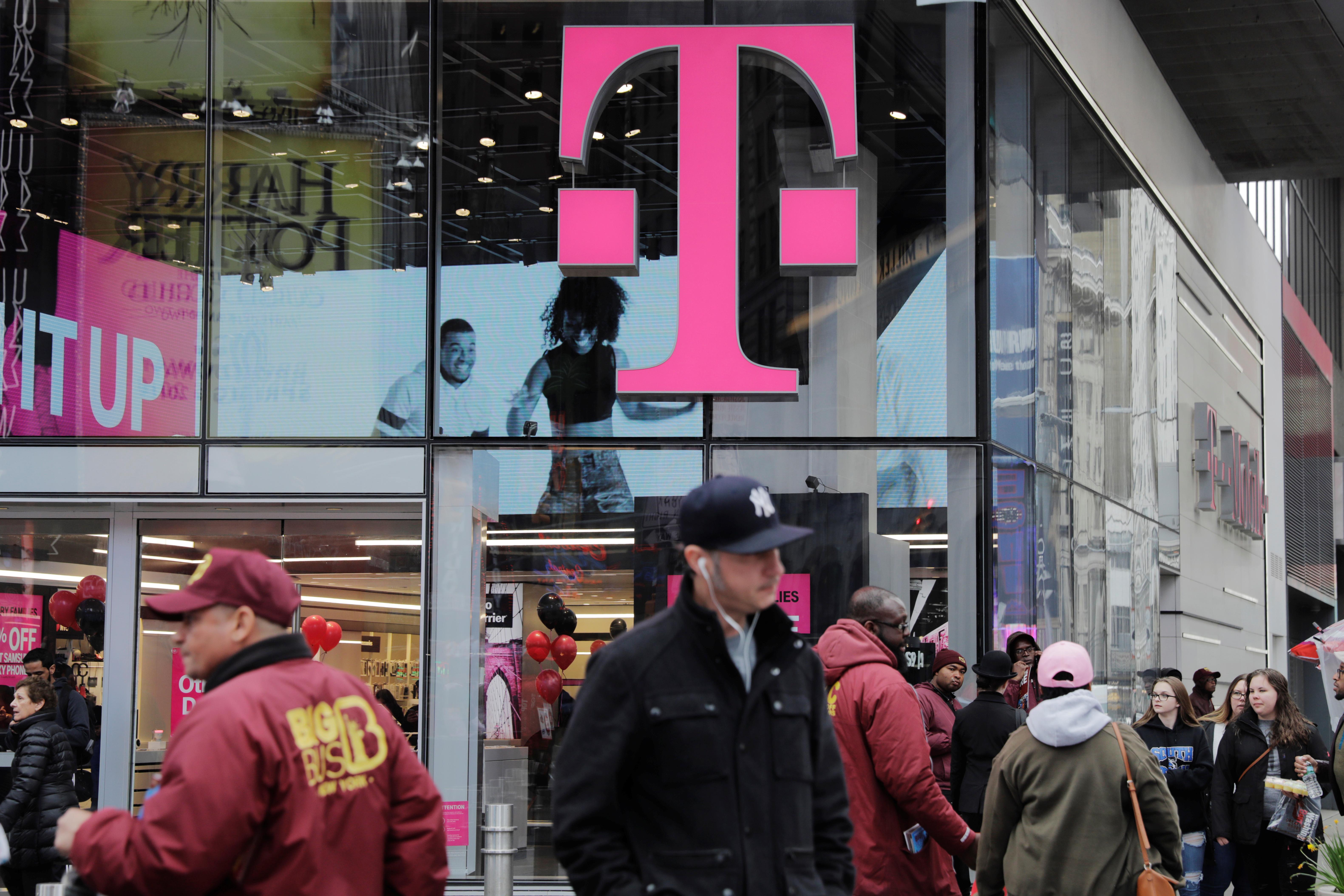 Pedestrians walk past a T-Mobile store in New York, U.S., April 27, 2018. REUTERS/Lucas Jackson