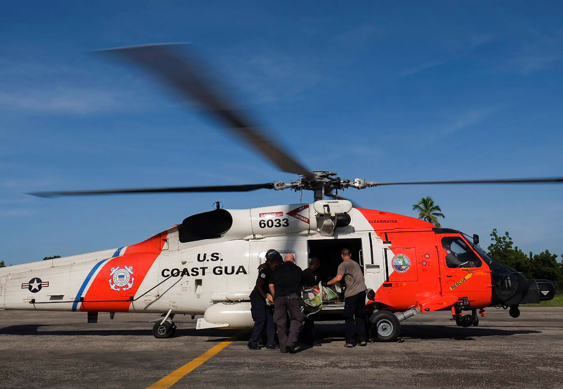 Members of the U.S. Coast Guard board a person who was injured in Saturday's 7.2 magnitude earthquake in a helicopter for evacuation, at the airport, in Les Cayes, Haiti August 16, 2021. REUTERS/Ricardo Arduengo