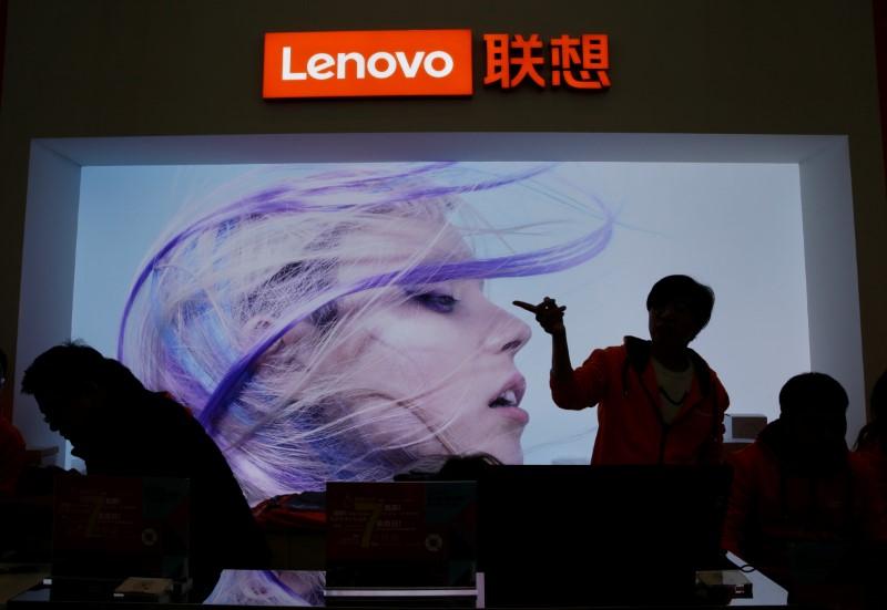 An employee gestures next to a Lenovo logo at Lenovo Tech World in Beijing, China November 15, 2019. REUTERS/Jason Lee