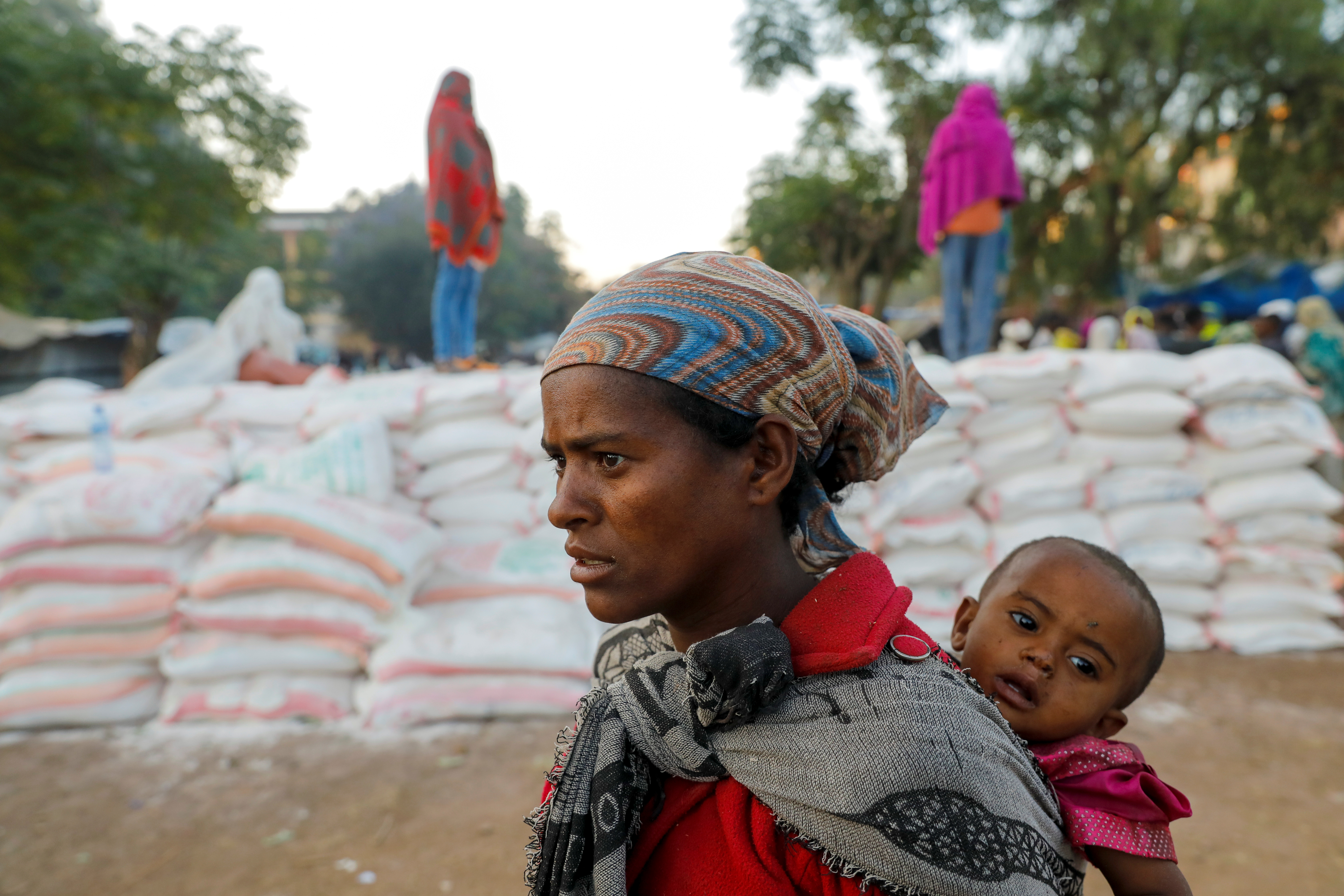 A woman carries an infant as she queues in line for food, at the Tsehaye primary school, which was turned into a temporary shelter for people displaced by conflict, in the town of Shire, Tigray region, Ethiopia, March 15, 2021.   REUTERS/Baz Ratner