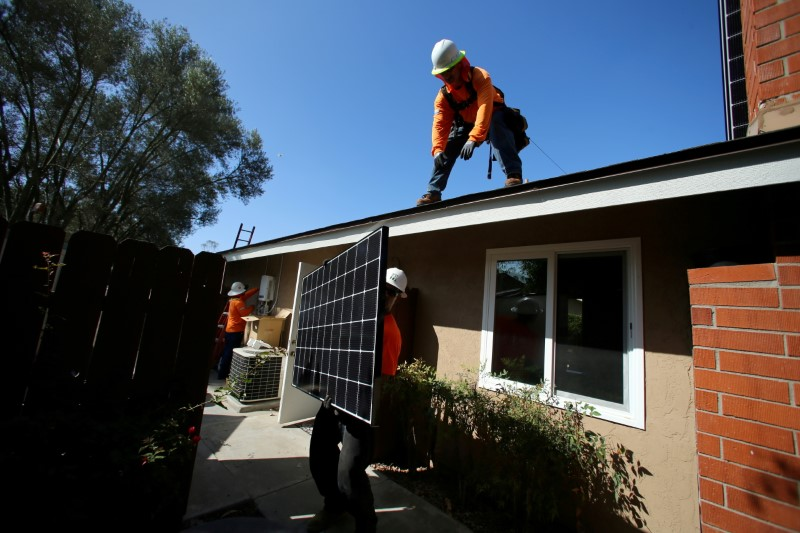 Workers lift a solar panel onto a roof during a residential solar installation in Scripps Ranch, San Diego, California, U.S. October 14, 2016. REUTERS/Mike Blake/File Photo