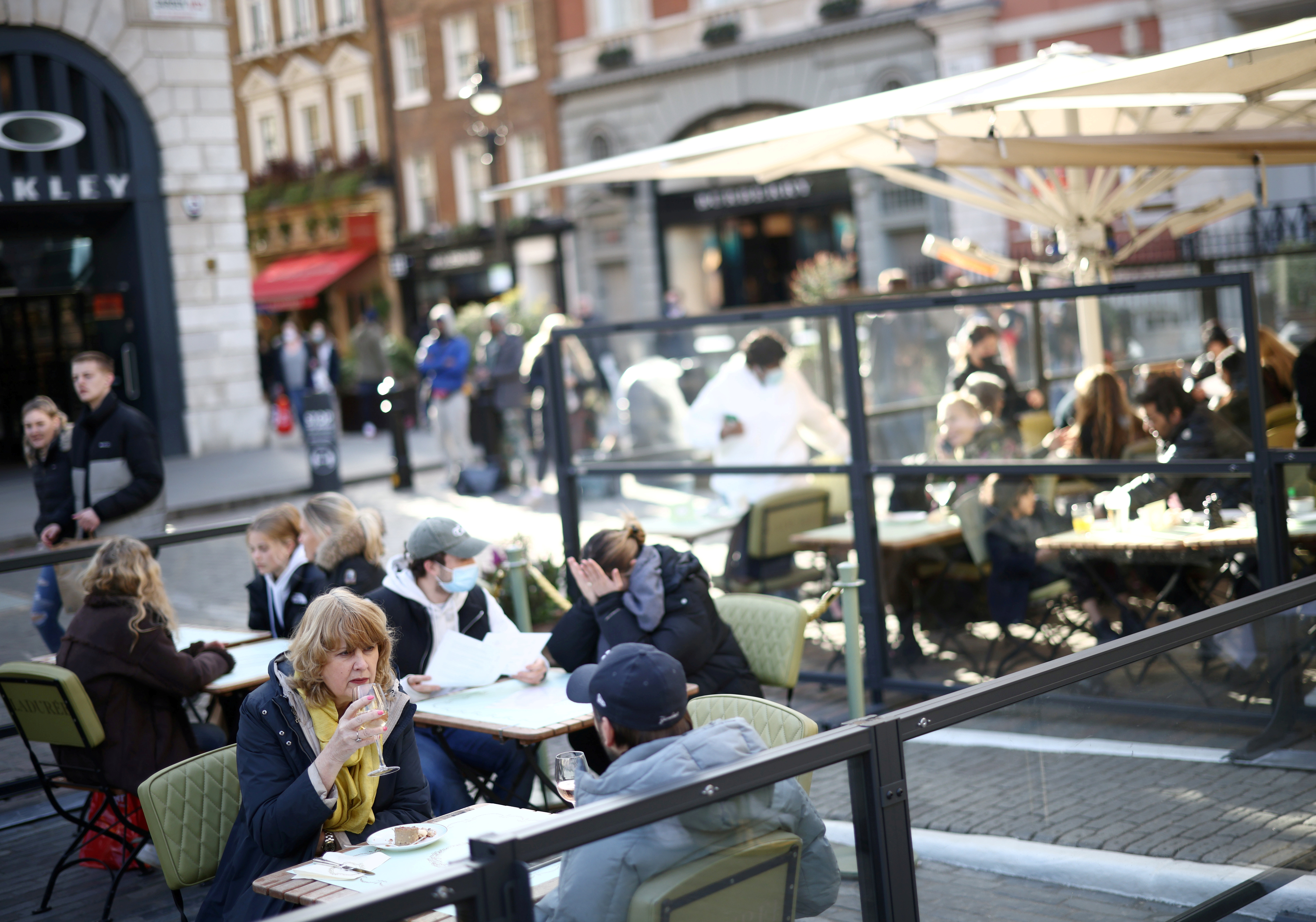 People sit at an outside restaurant area, as the coronavirus disease (COVID-19) restrictions ease, at Covent Garden in London, Britain April 12, 2021. REUTERS/Henry Nicholls/File Photo