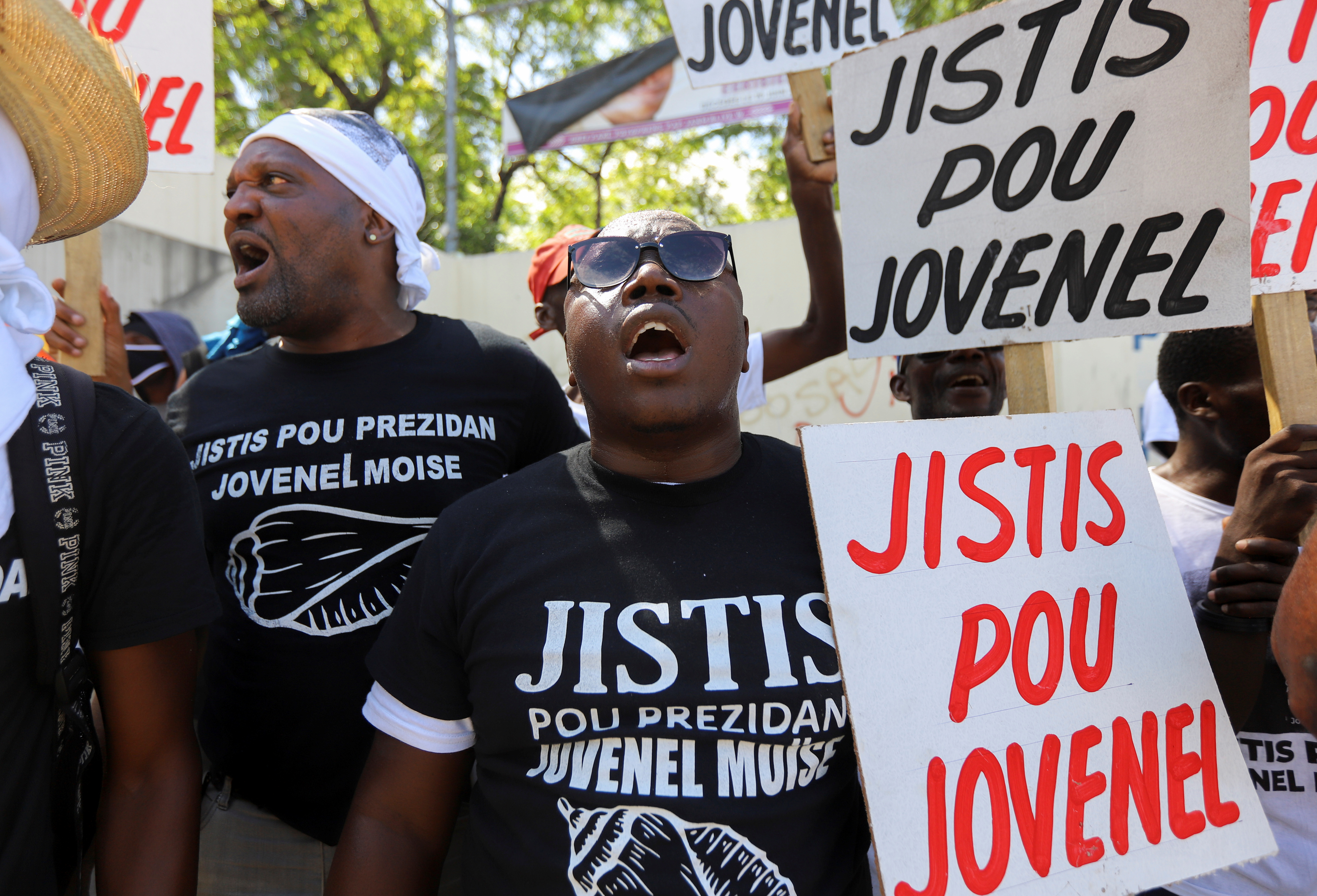 """Demonstrators hold signs reading """"Justice for Jovenel"""" outside a judicial hearing into the assassination of President Jovenel Moise attended by former first lady Martine Moise, in Port-au-Prince, Haiti October 6, 2021. REUTERS/Ralph Tedy Erol"""