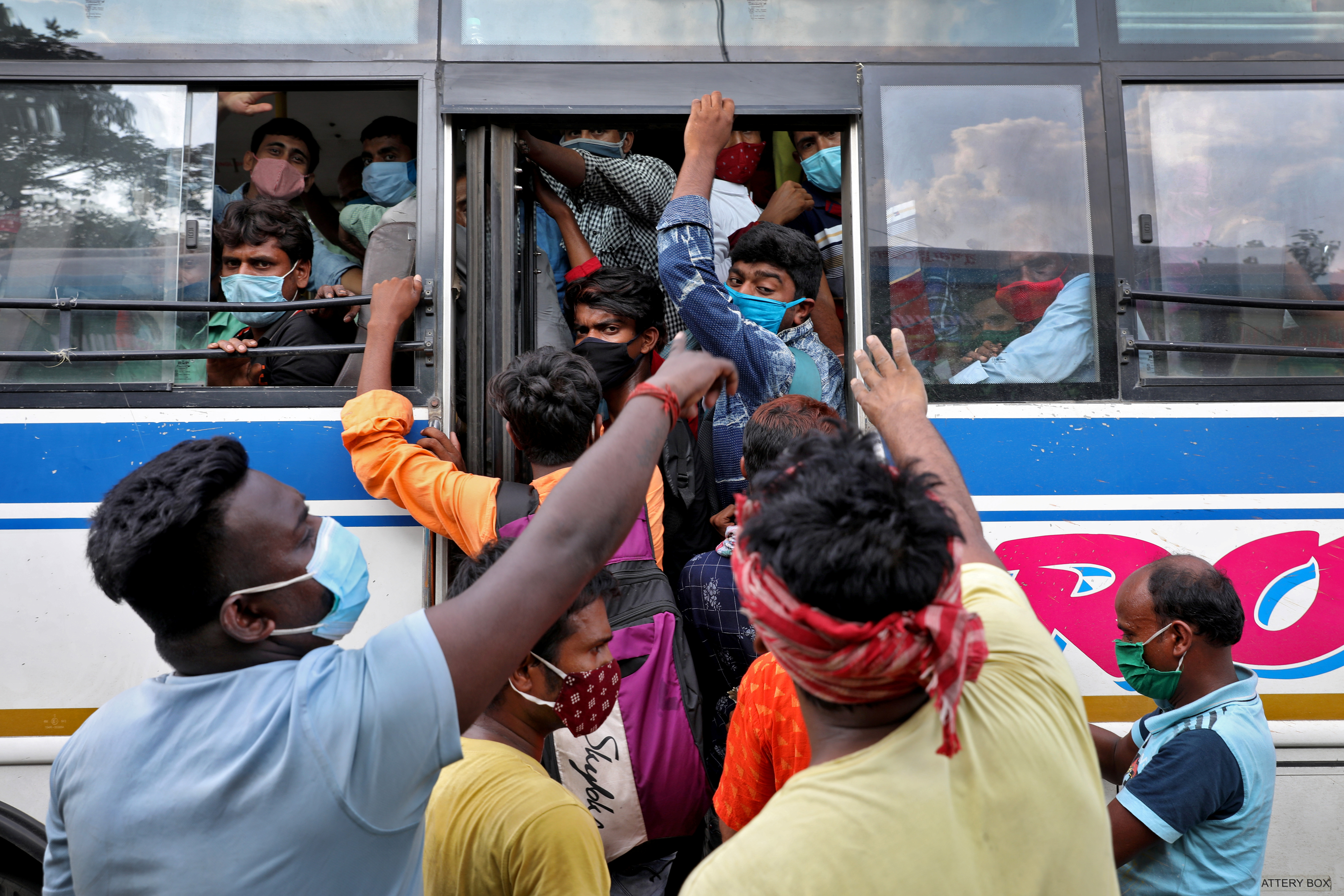 Migrant workers board an overcrowded bus to return to their cities and villages after the West Bengal state government imposed a partial lockdown to limit the spread of the coronavirus disease (COVID-19) in Kolkata, May 6, 2021. REUTERS/Rupak De Chowdhuri