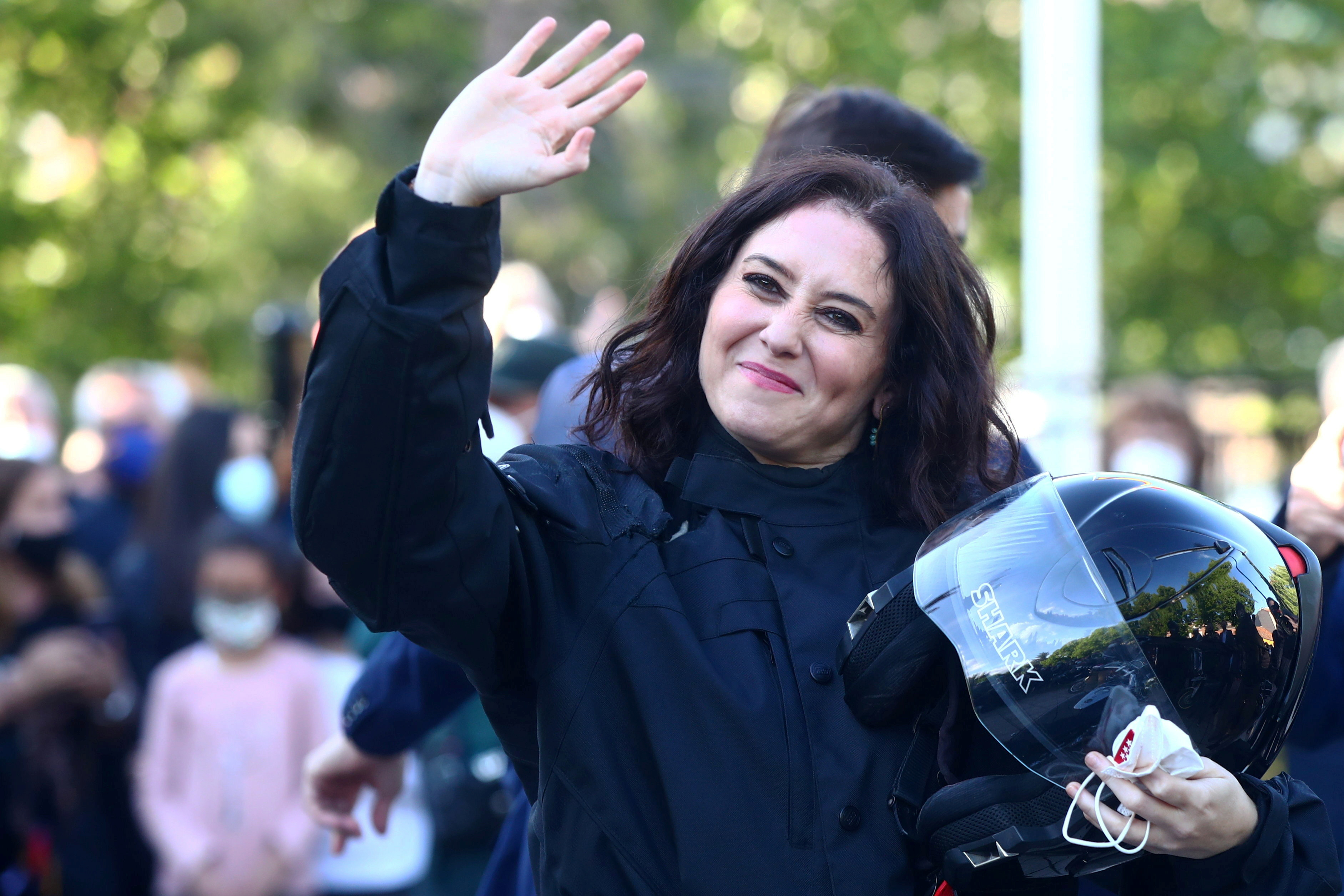 Madrid regional government leader Isabel Diaz Ayuso waves to supporters upon arriving by motorbike to an electoral event ahead upcoming regional elections in Valdemoro, Spain, April 29, 2021. REUTERS/Sergio Perez