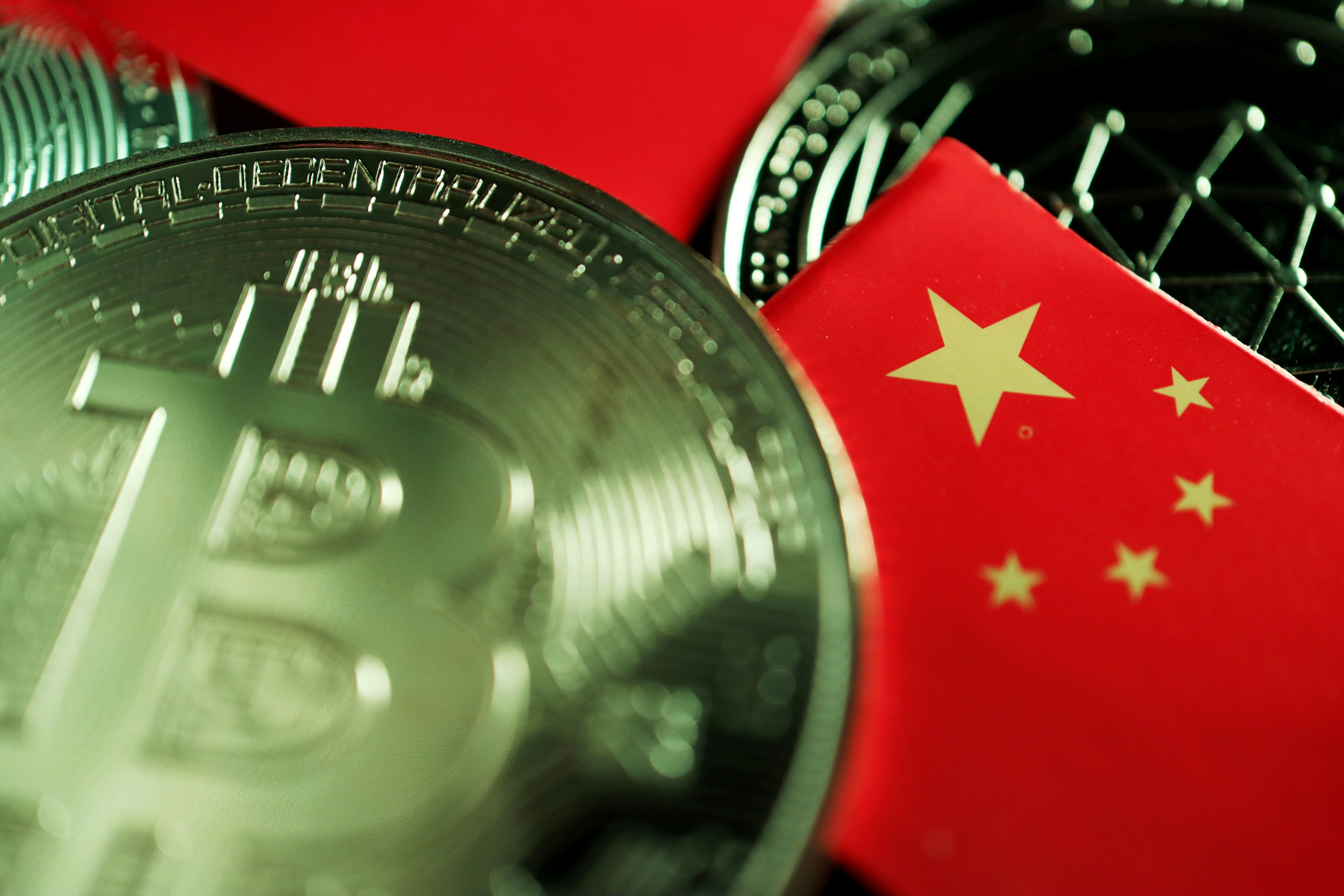 A Chinese flag is seen among representations of Bitcoin and other cryptocurrencies in this illustration picture taken June 2, 2021. REUTERS/Florence Lo/Illustration/File Photo