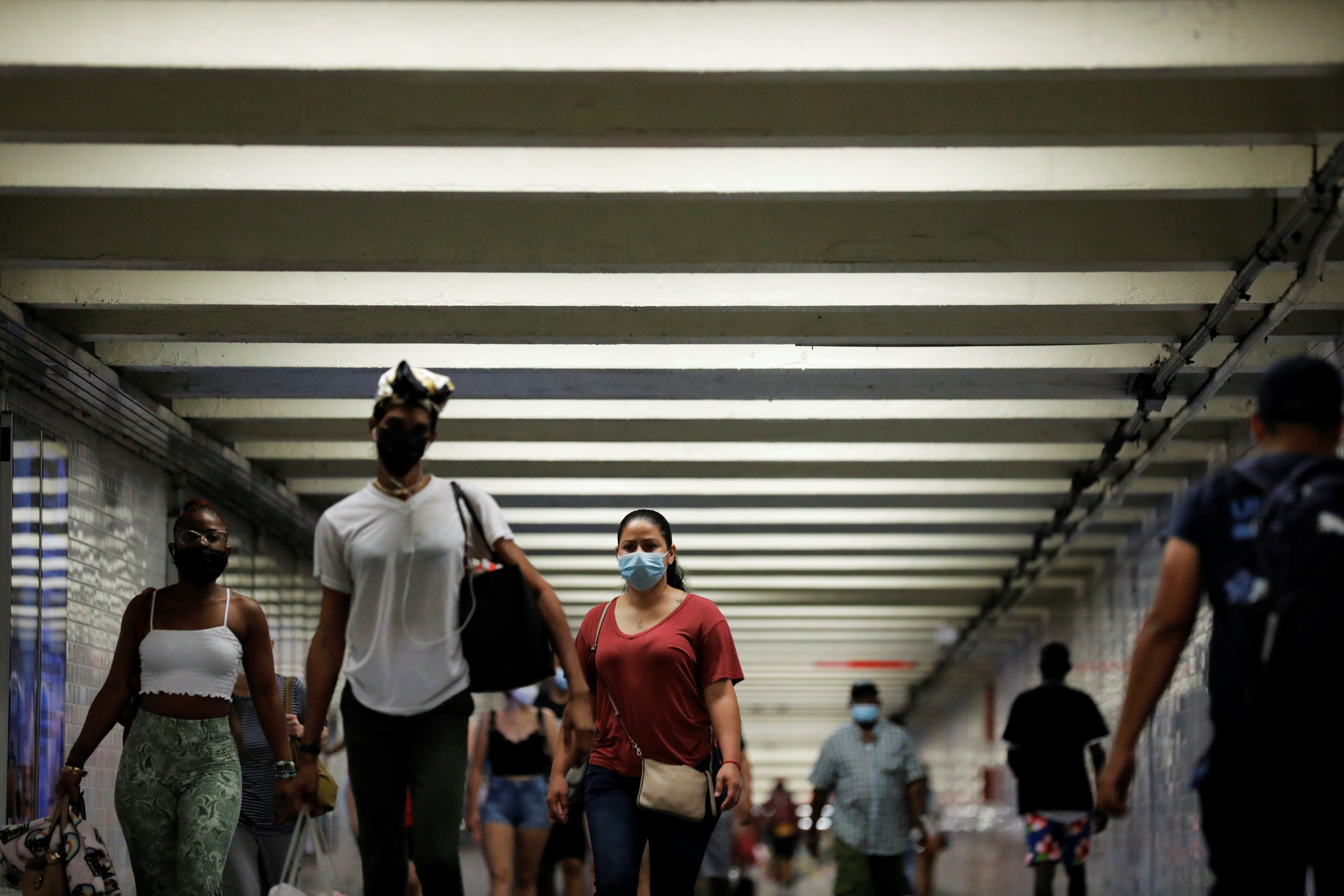 People wear masks as they pass through a pedestrian subway as cases of the infectious coronavirus Delta variant continue to rise in New York City, New York, U.S., July 26, 2021. REUTERS/Andrew Kelly