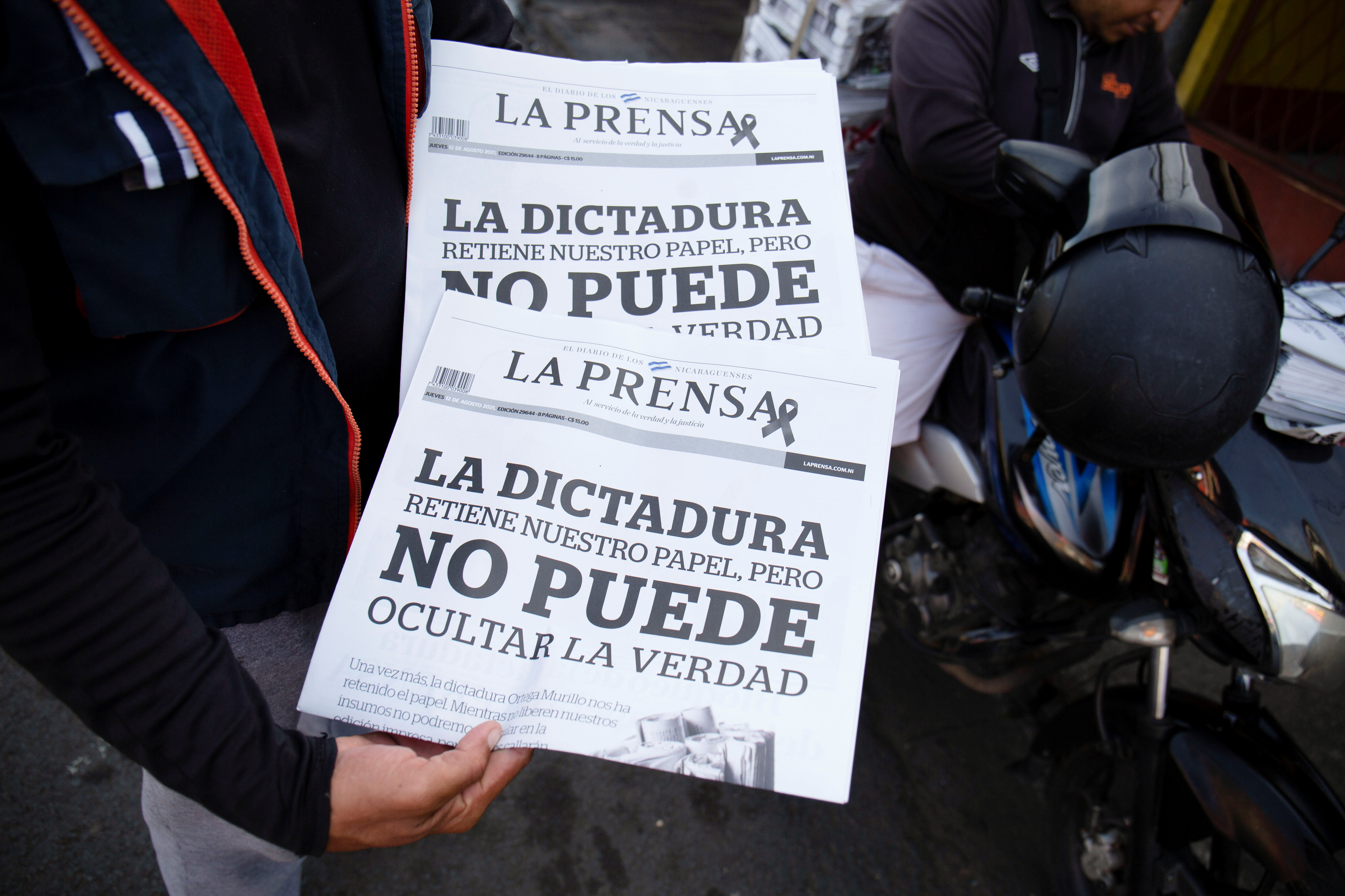A delivery man shows La Prensa, Nicaragua's only print newspaper, which will no longer issue a print edition complaining that the administration of President Daniel Ortega was withholding the paper it uses for publishing, in Managua, Nicaragua August 12, 2021. The front page reads: