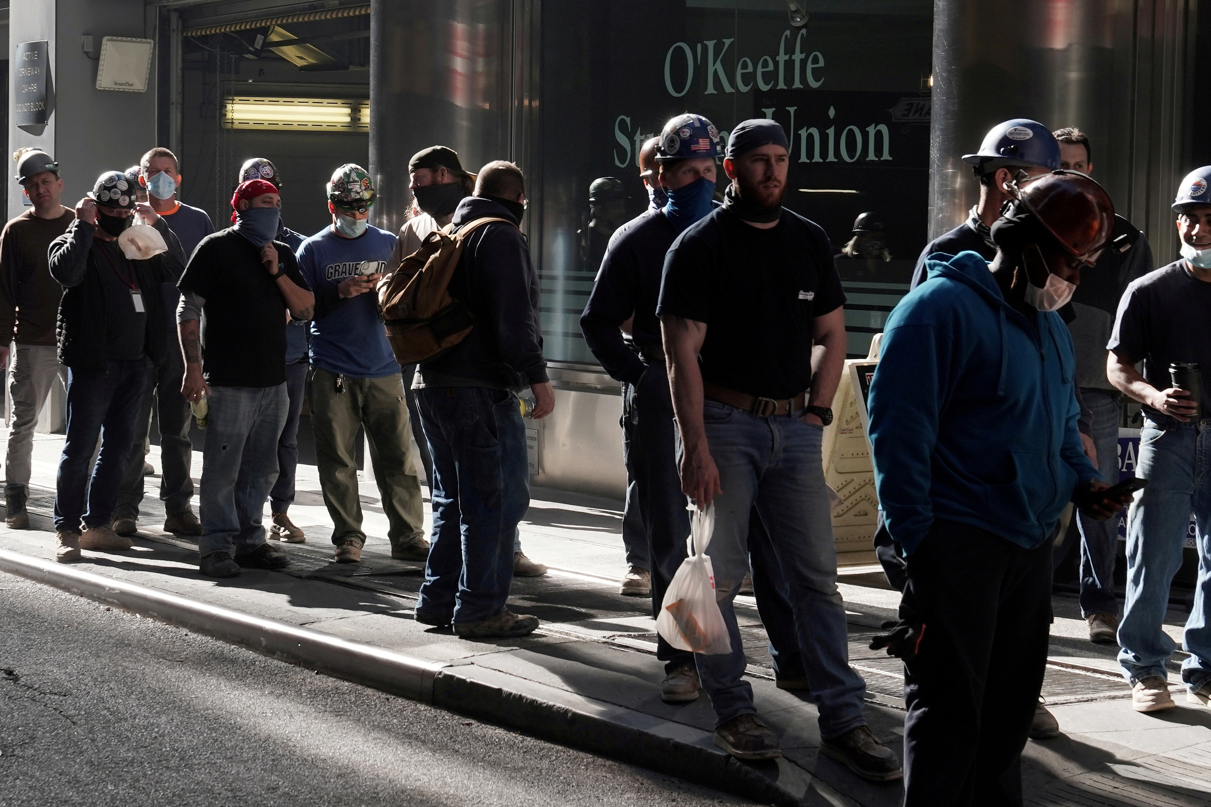 Construction workers wait in line to do a temperature test to return to the job site after lunch, amid the coronavirus disease (COVID-19) outbreak, in the Manhattan borough of New York City, New York, U.S., November 10, 2020. REUTERS/Carlo Allegri