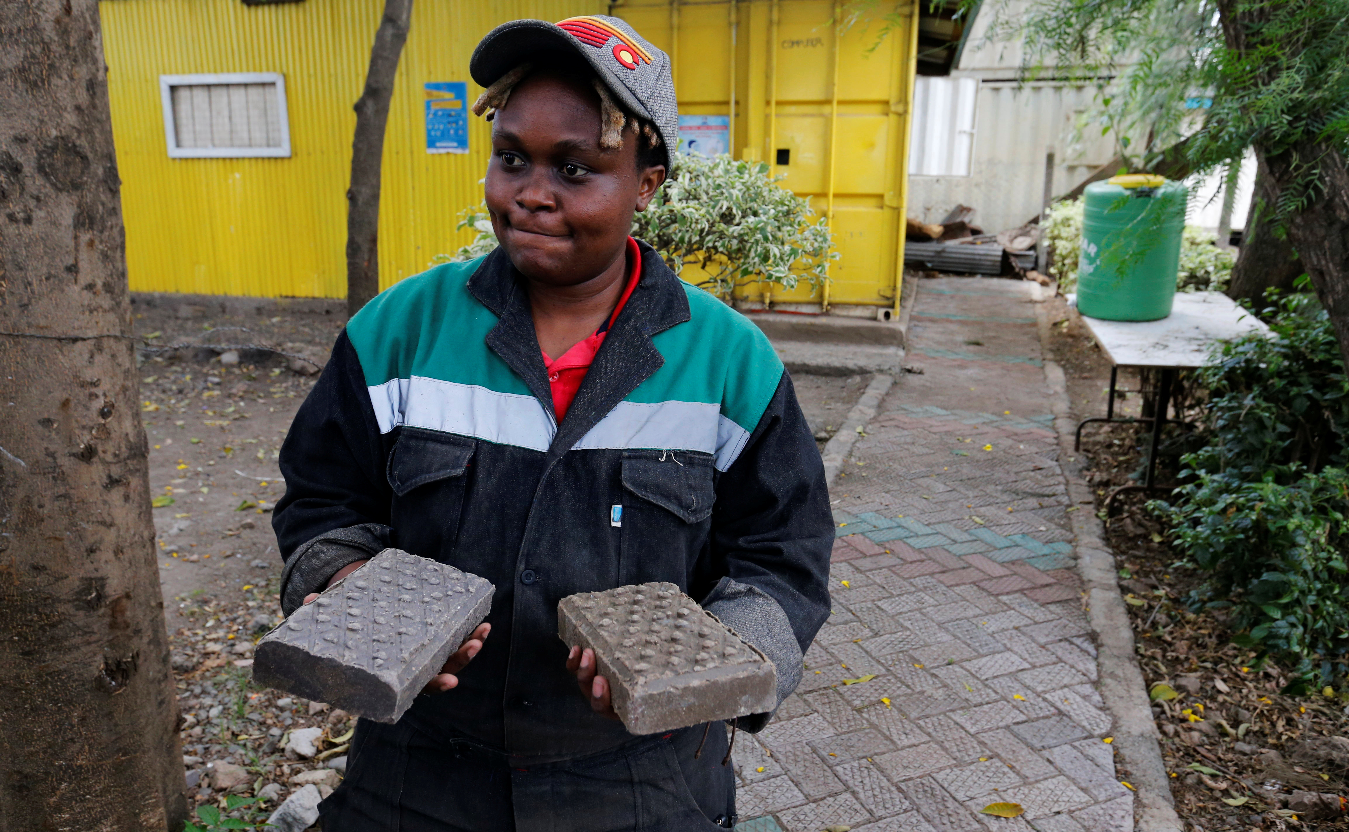 Nzambi Matee, founder of Gjenge Makers, a social enterprise that recycles and up-cycles waste plastic into construction products such as paving bricks holds Gjenge pavers in Nairobi, Kenya January 21, 2021. Picture taken January 21, 2021. REUTERS/Thomas Mukoya