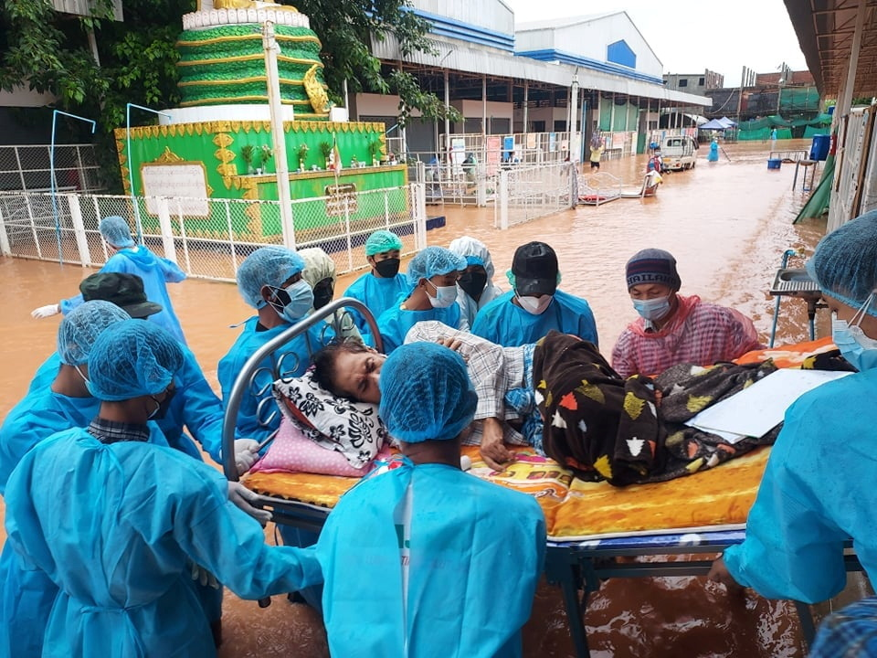 Volunteers in protective suits carry a COVID-19 patient lying on a hospital bed as they try to relocate patients who are dependent on oxygen from the COVID-19 center due to the flood in Myawaddy, Karen state, Myanmar, July 26, 2021, in this handout imaged obtained by Reuters on July 27, 2021. Karen Information Center/Handout via REUTERS