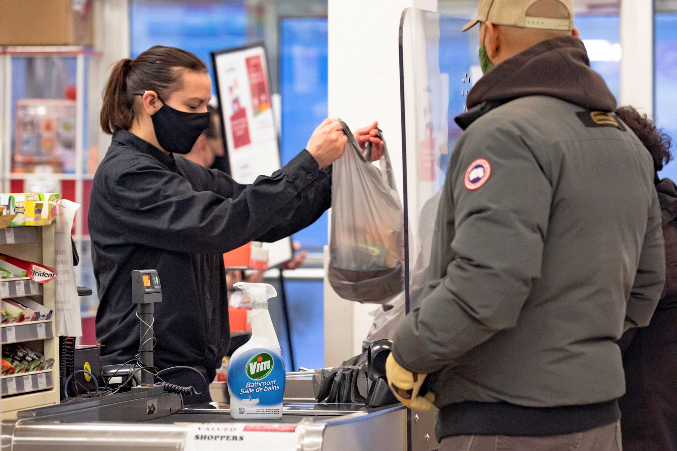 A cashier wearing a mask to help slow the spread of coronavirus disease (COVID-19) bags groceries as the territory of Nunavut enters a two week mandatory restriction period in Iqaluit, Nunavut, Canada November 18, 2020.  REUTERS/Natalie Maerzluft/File Photo