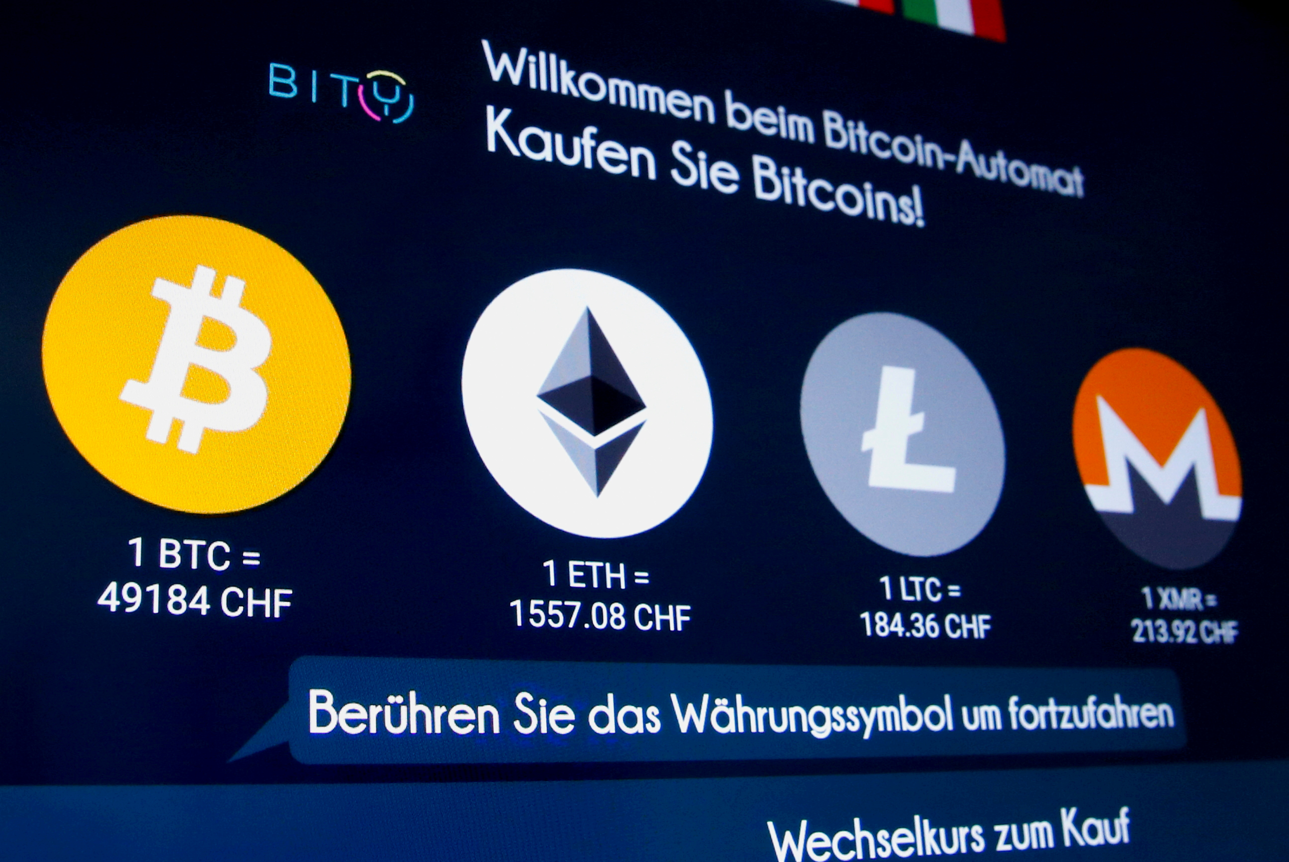 The exchange rates and logos of Bitcoin (BTH), Ether (ETH), Litecoin (LTC) and Monero (XMR) are seen on the display of a cryptocurrency ATM of blockchain payment service provider Bity at the House of Satochi bitcoin and blockchain shop in Zurich, Switzerland March 4, 2021. REUTERS/Arnd Wiegmann/File Photo