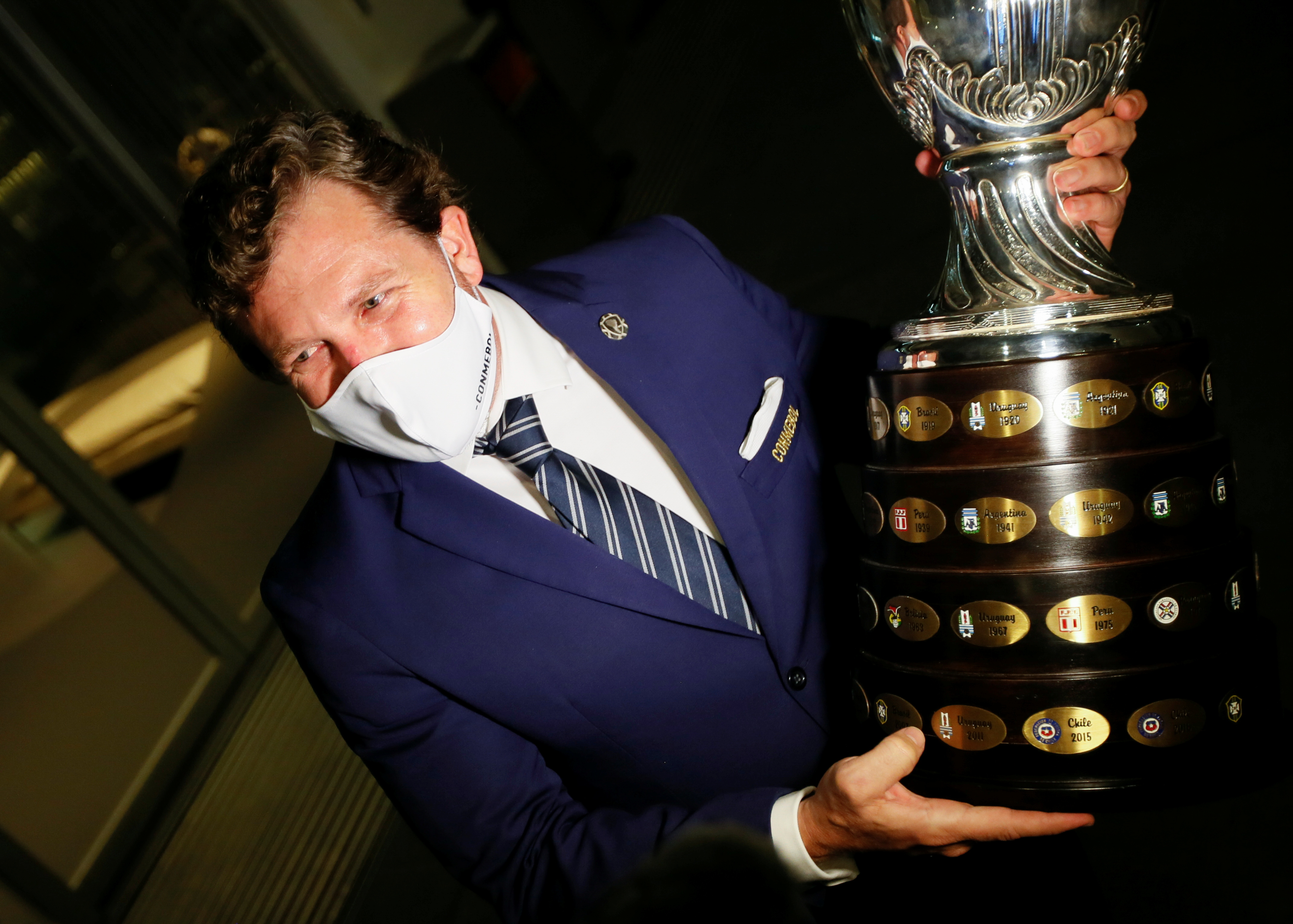 Alejandro Dominguez, president of CONMEBOL, holds the Copa America trophy after he gives a news conference after the arrival of the 50 thousand doses of the Chinese Sinovac coronavirus disease (COVID 19) vaccine that were donated by the Chinese government to the CONMEBOL in Carrasco Airport in Montevideo, Uruguay April 28, 2021. REUTERS/Mariana Greif