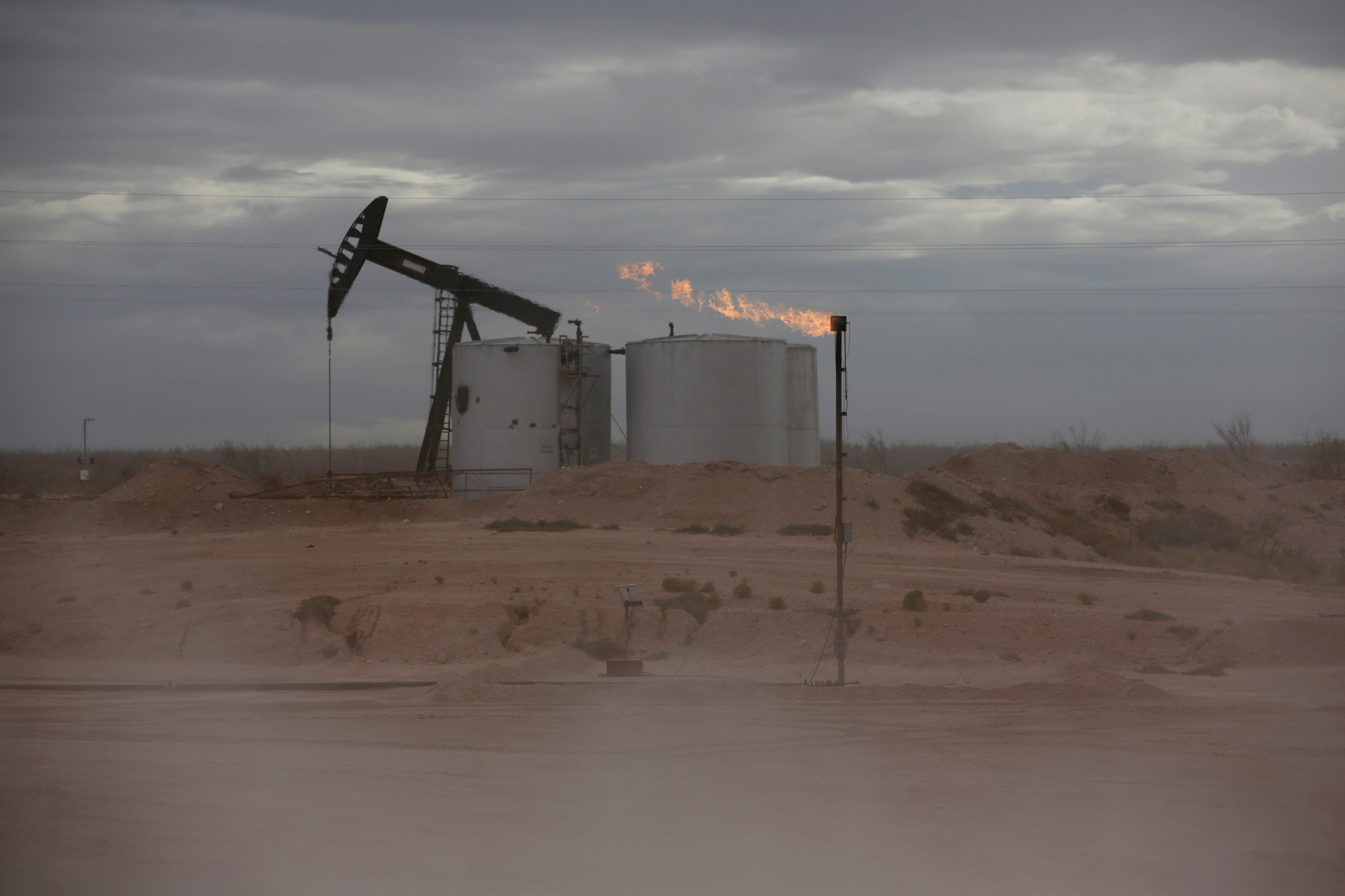 Dust blows around a crude oil pump jack and flare burning excess gas at a drill pad in the Permian Basin in Loving County, Texas, U.S. November 25, 2019. REUTERS/Angus Mordan/File Photo