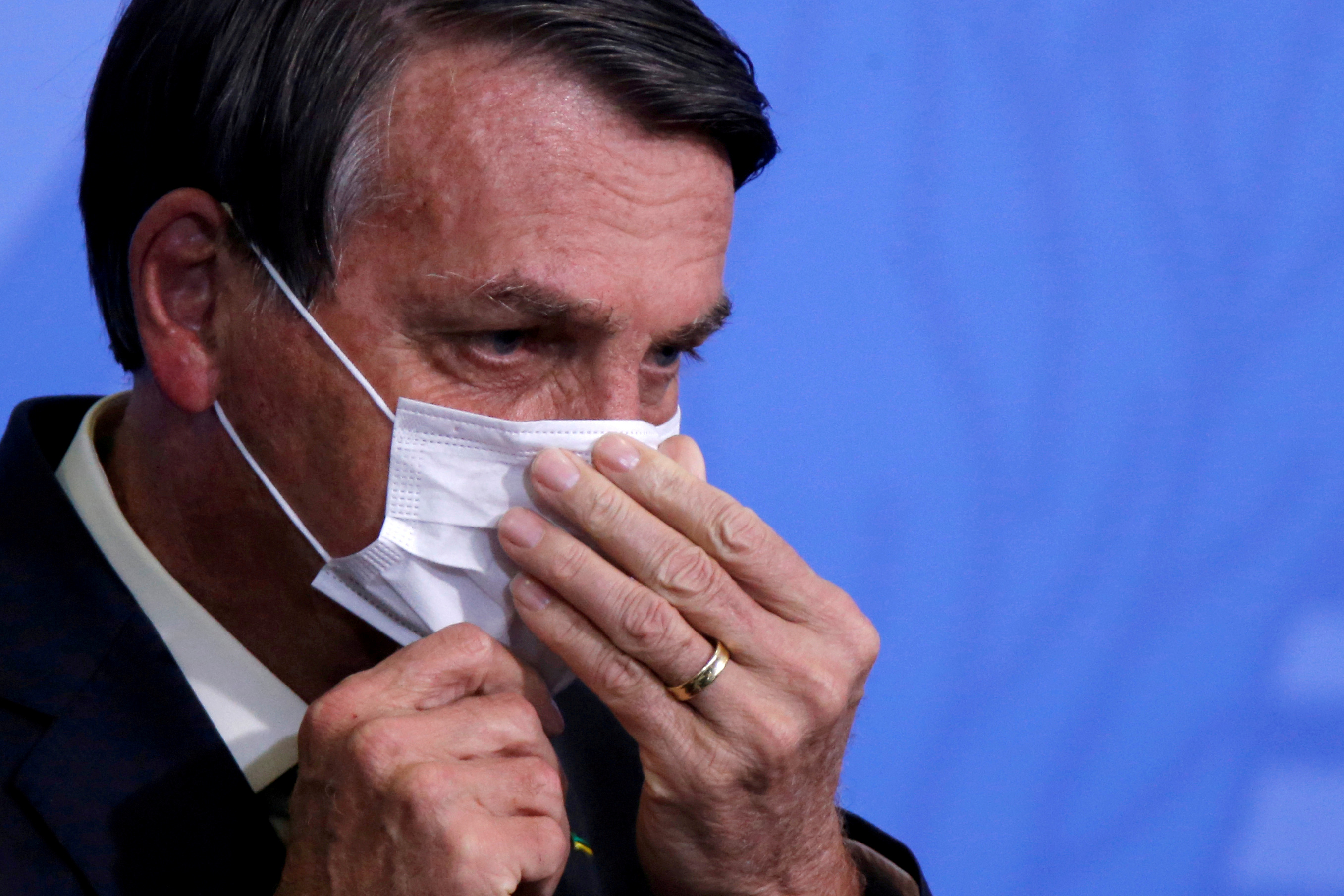 Brazil President Jair Bolsonaro looks on as he adjusts his protective face mask during a ceremony launching a program to expand access to credit at the Planalto Palace in Brasilia, Brazil, August 19, 2020. REUTERS/Adriano Machado//File Photo
