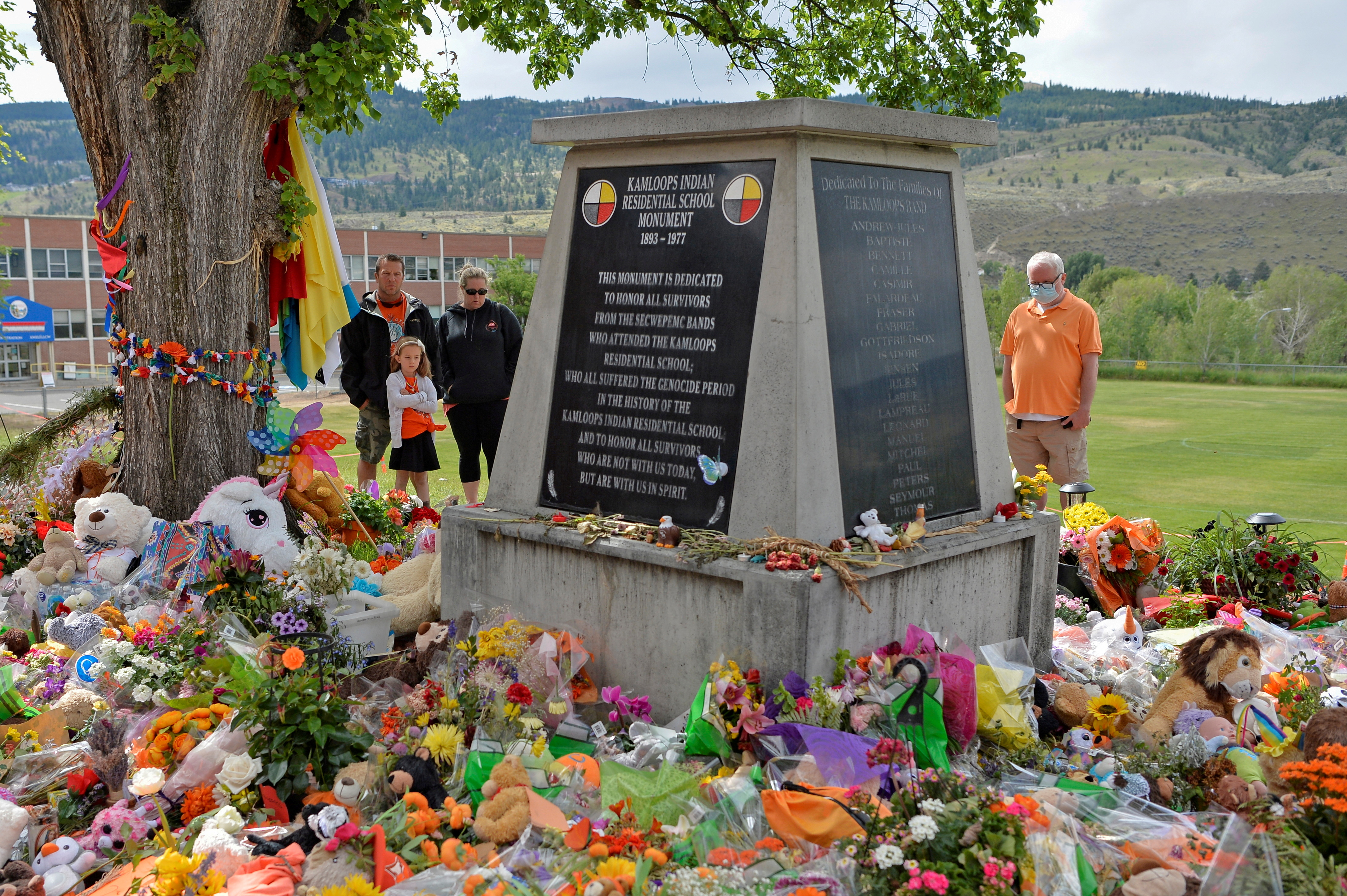 People visit a makeshift memorial on the grounds of the former Kamloops Indian Residential School, after the Tk'emlups te Secwepemc band council encouraged mourners to take part in a national day of prayer to honor the remains of 215 children that were found at the site in Kamloops, British Columbia, Canada June 6, 2021.  REUTERS/Jennifer Gauthier/File Photo