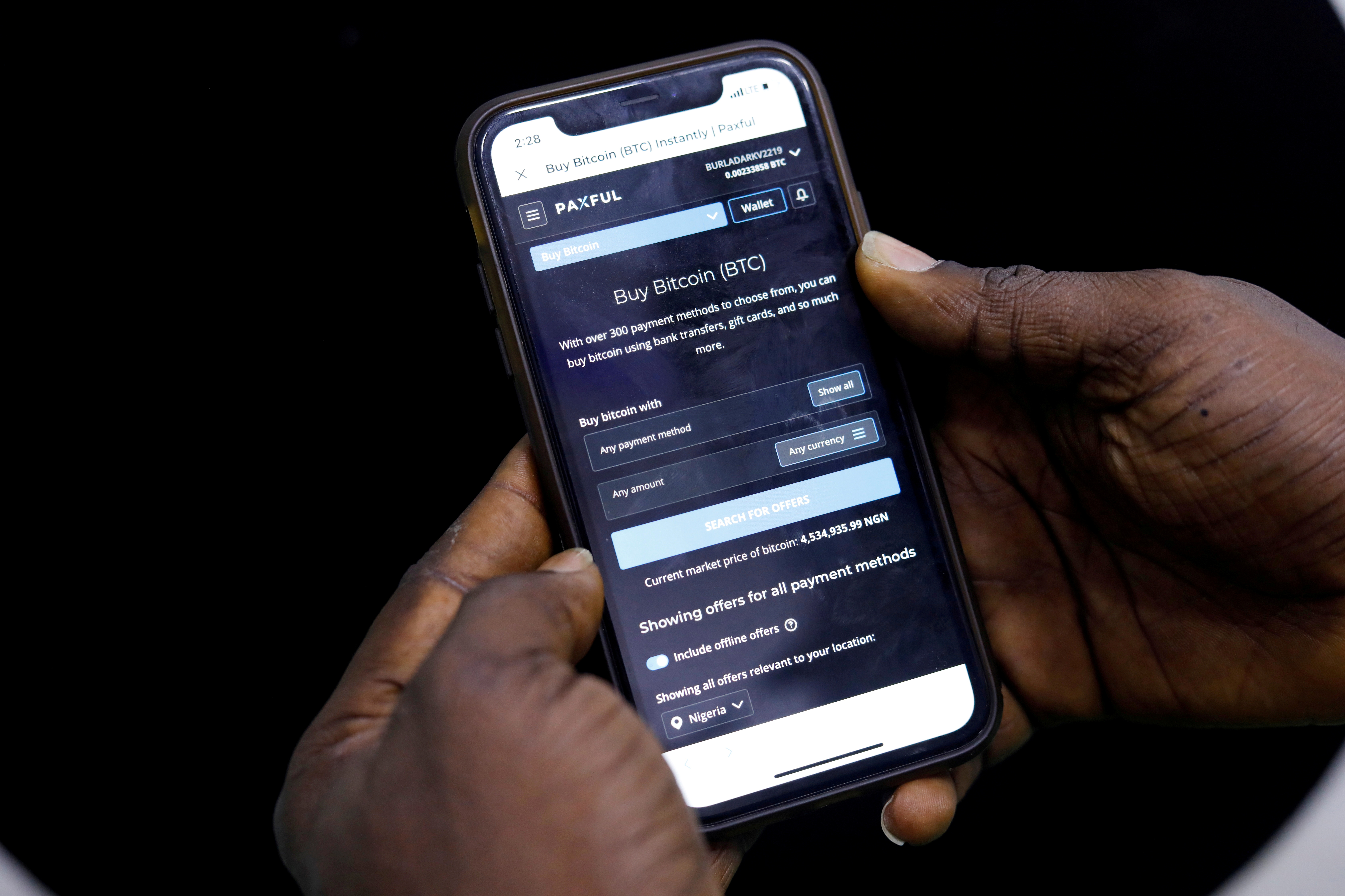 Abolaji Odunjo, a gadget vendor who trades with bitcoin, demonstrates a bitcoin application on his mobile phone in Lagos, Nigeria August 31, 2020. REUTERS/Temilade Adelaja/File Photo