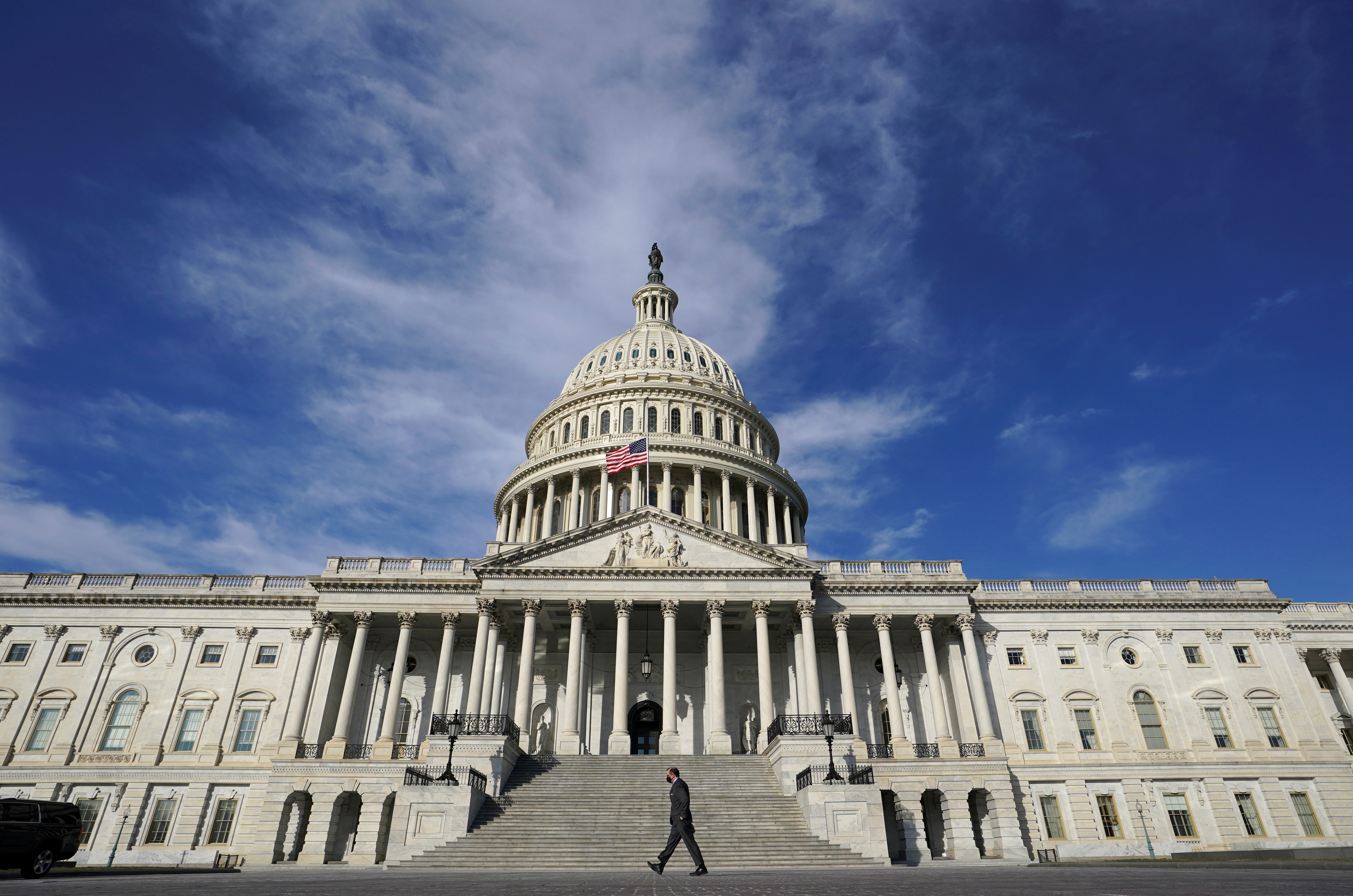A man makes his way past the U.S. Capitol in Washington, U.S., February 26, 2021. REUTERS/Kevin Lamarque/File Photo