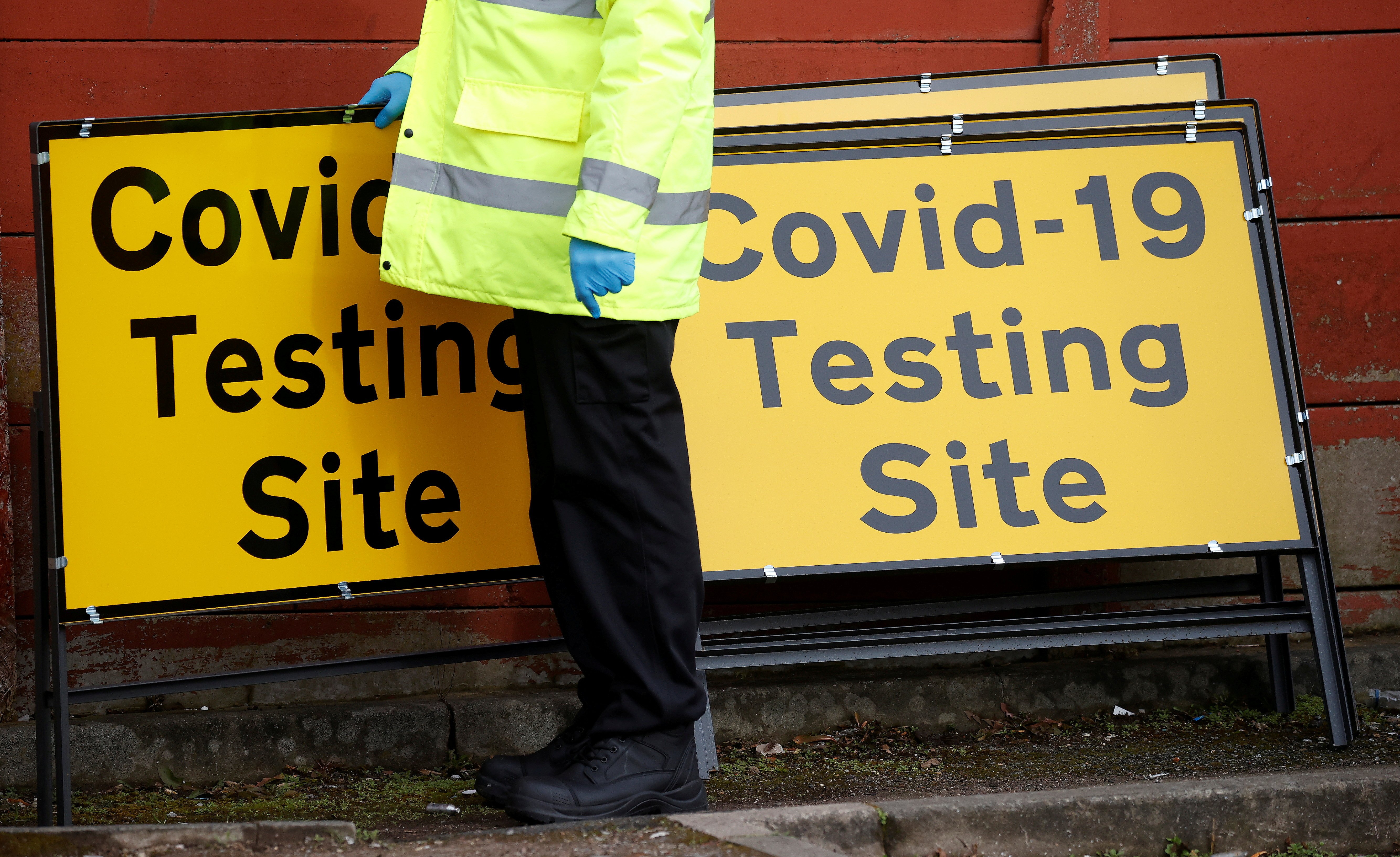 A member of NHS Test and Trace staff sets up a mobile testing centre amid the outbreak of the coronavirus disease (COVID-19) in the Moston area of Manchester, Britain, February 17, 2021. REUTERS/Phil Noble/File Photo
