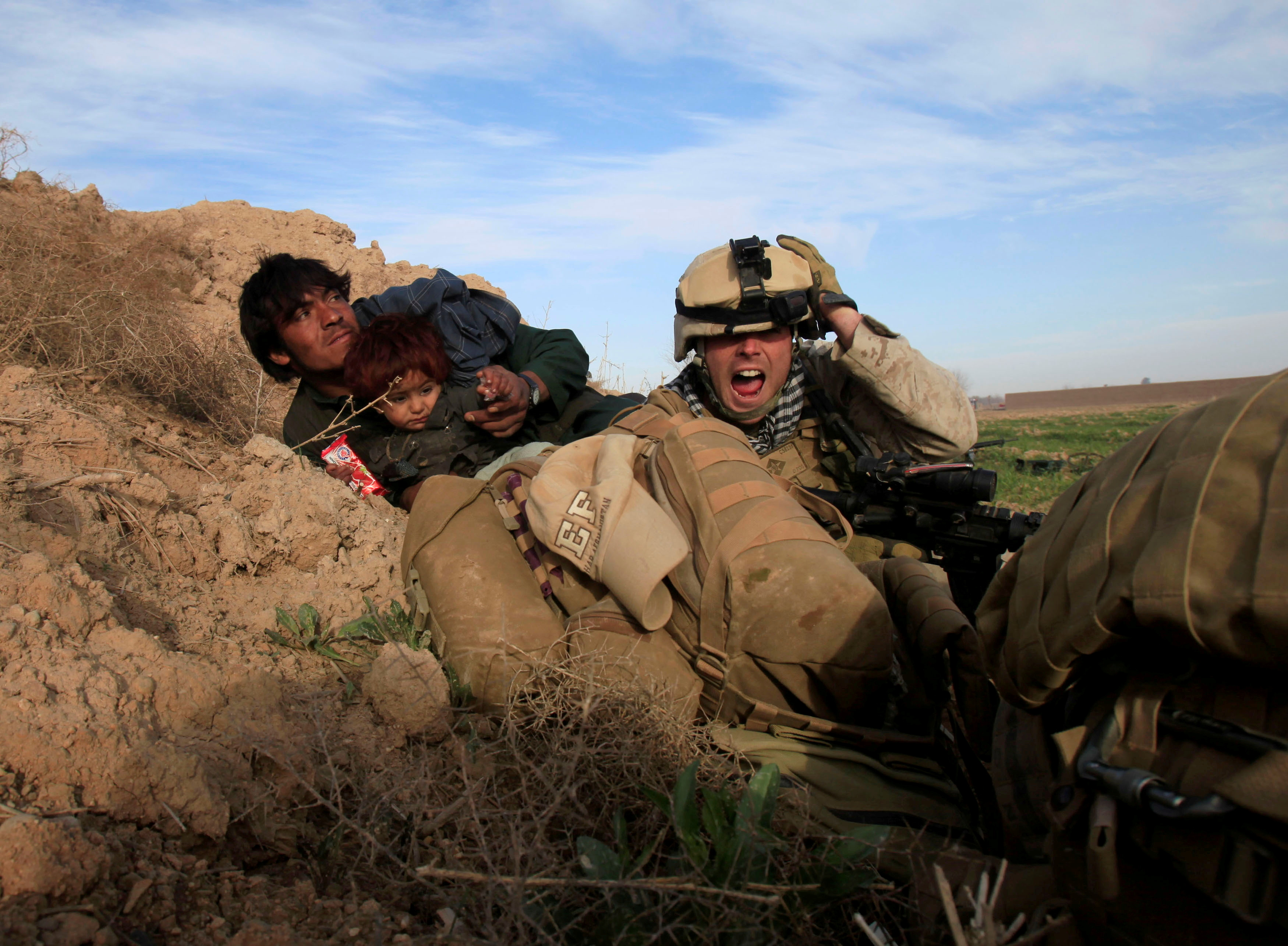 U.S. Marine Lance Corporal Chris Sanderson, from Flemington, New Jersey shouts as he tries to protect an Afghan man and his child after Taliban fighters opened fire in the town of Marjah, in Nad Ali district, Helmand province, Afghanistan, February 13, 2010.   REUTERS/Goran Tomasevic/File Photo