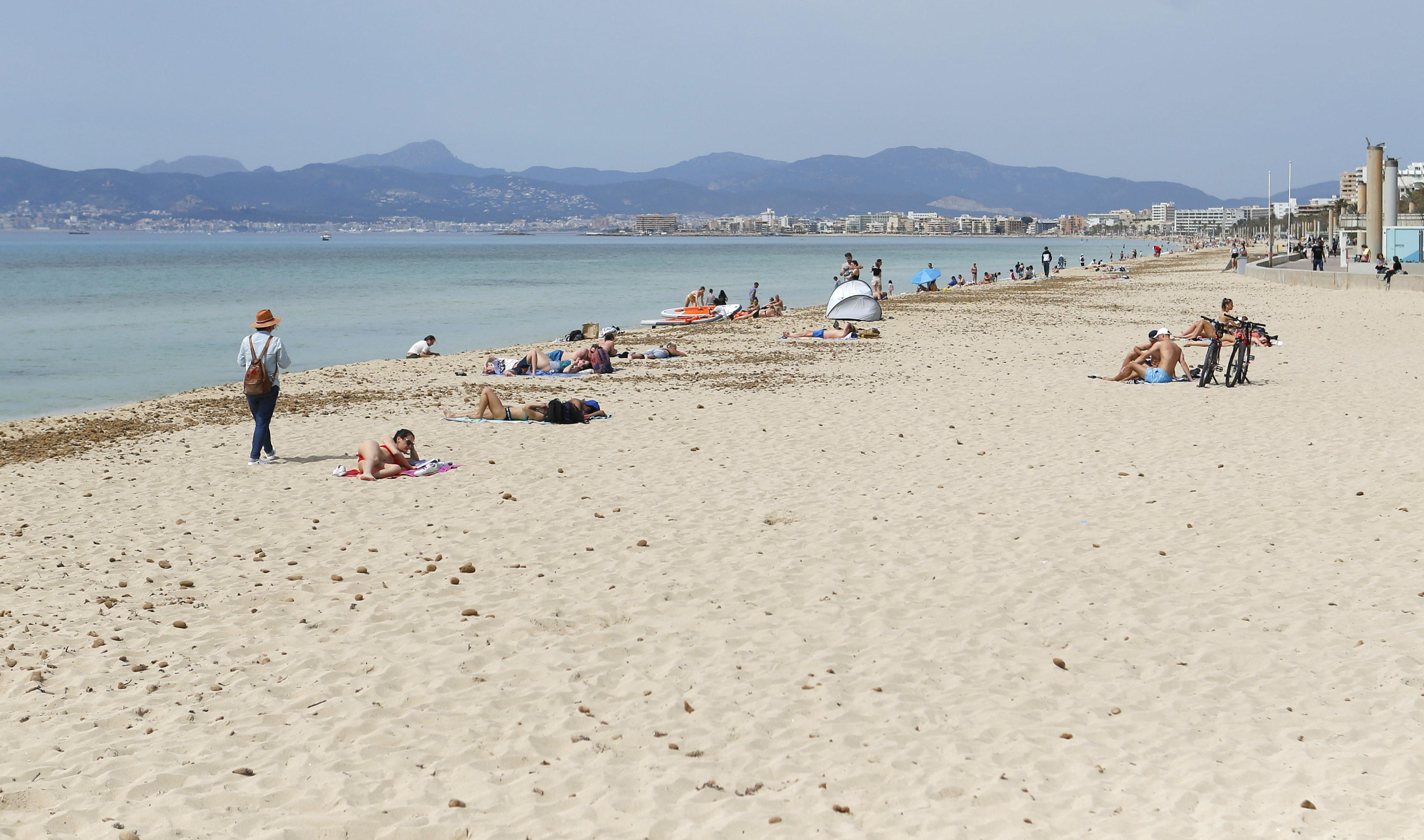 People sunbathe and chill on Playa de Palma beach in Palma de Mallorca, Spain, April 1, 2021. REUTERS/Enrique Calvo