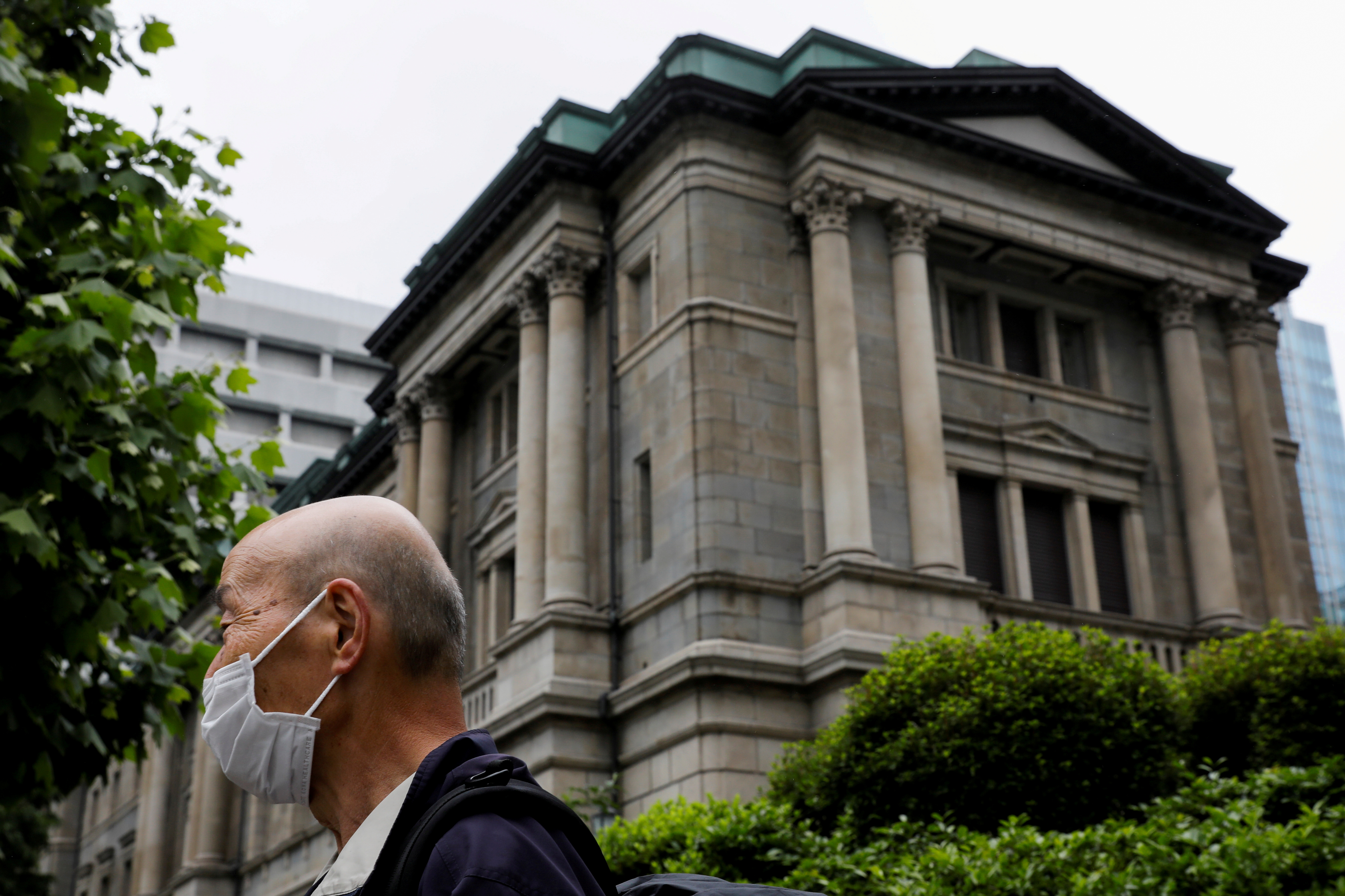 A man wearing a protective mask stands in front of the headquarters of the Bank of Japan amid the coronavirus disease (COVID-19) outbreak in Tokyo, Japan, May 22, 2020.REUTERS/Kim Kyung-Hoon